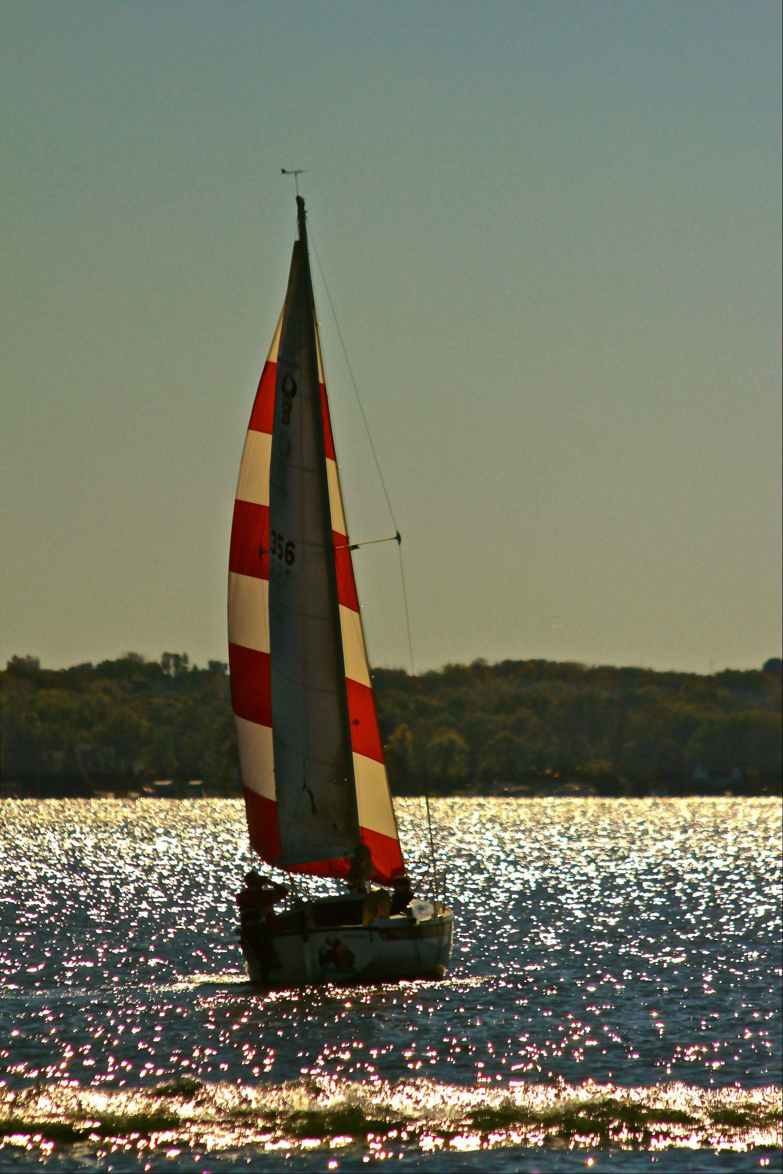 A sail boat moves out into the sun at Lake Geneva. The sun highlighted the red sail and glistened off the water.