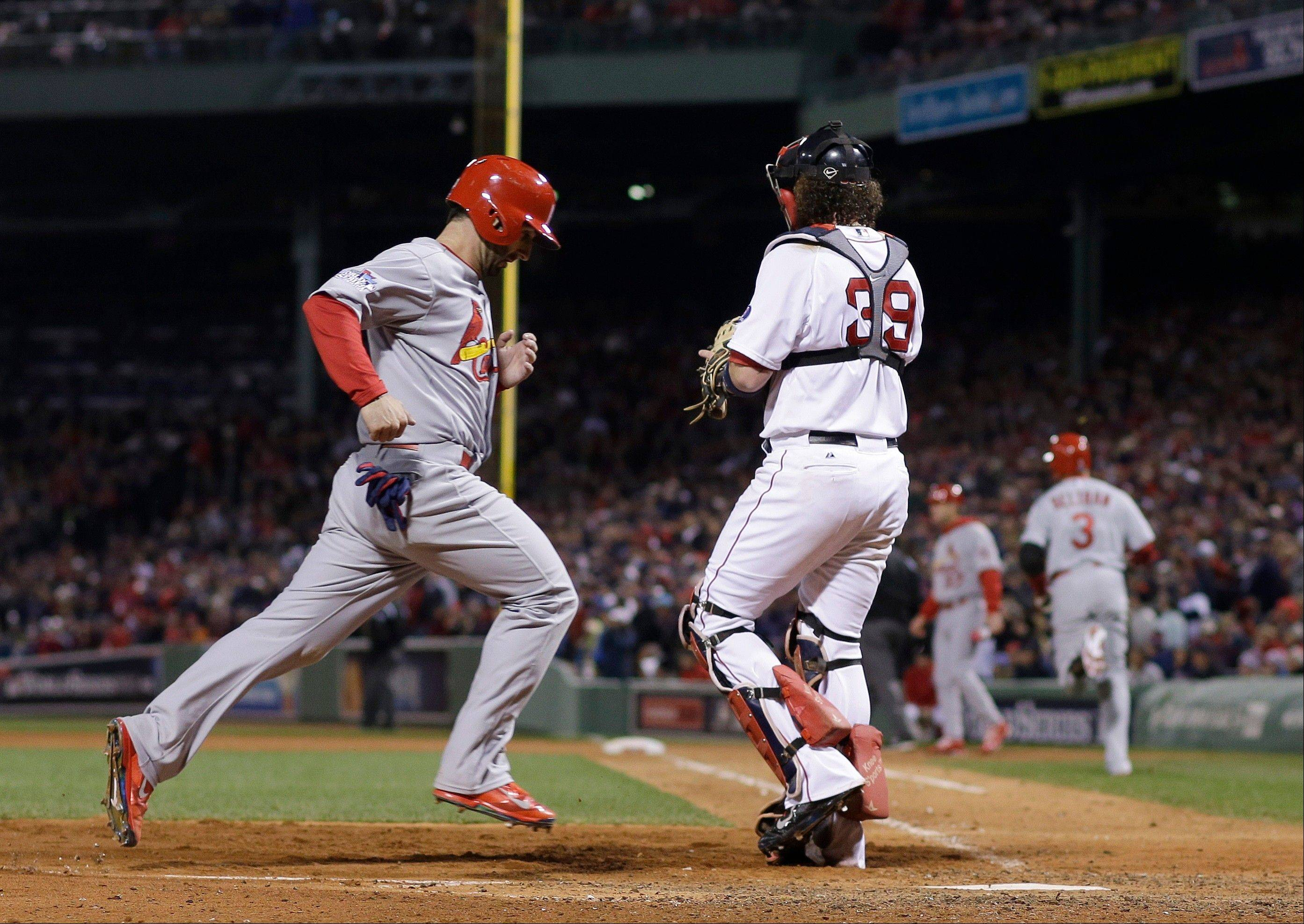 St. Louis Cardinals' Daniel Descalso scores past Boston Red Sox catcher Jarrod Saltalamacchia (39) on a hit by Carlos Beltran during the seventh inning of Game 2 of baseball's World Series Thursday in Boston.