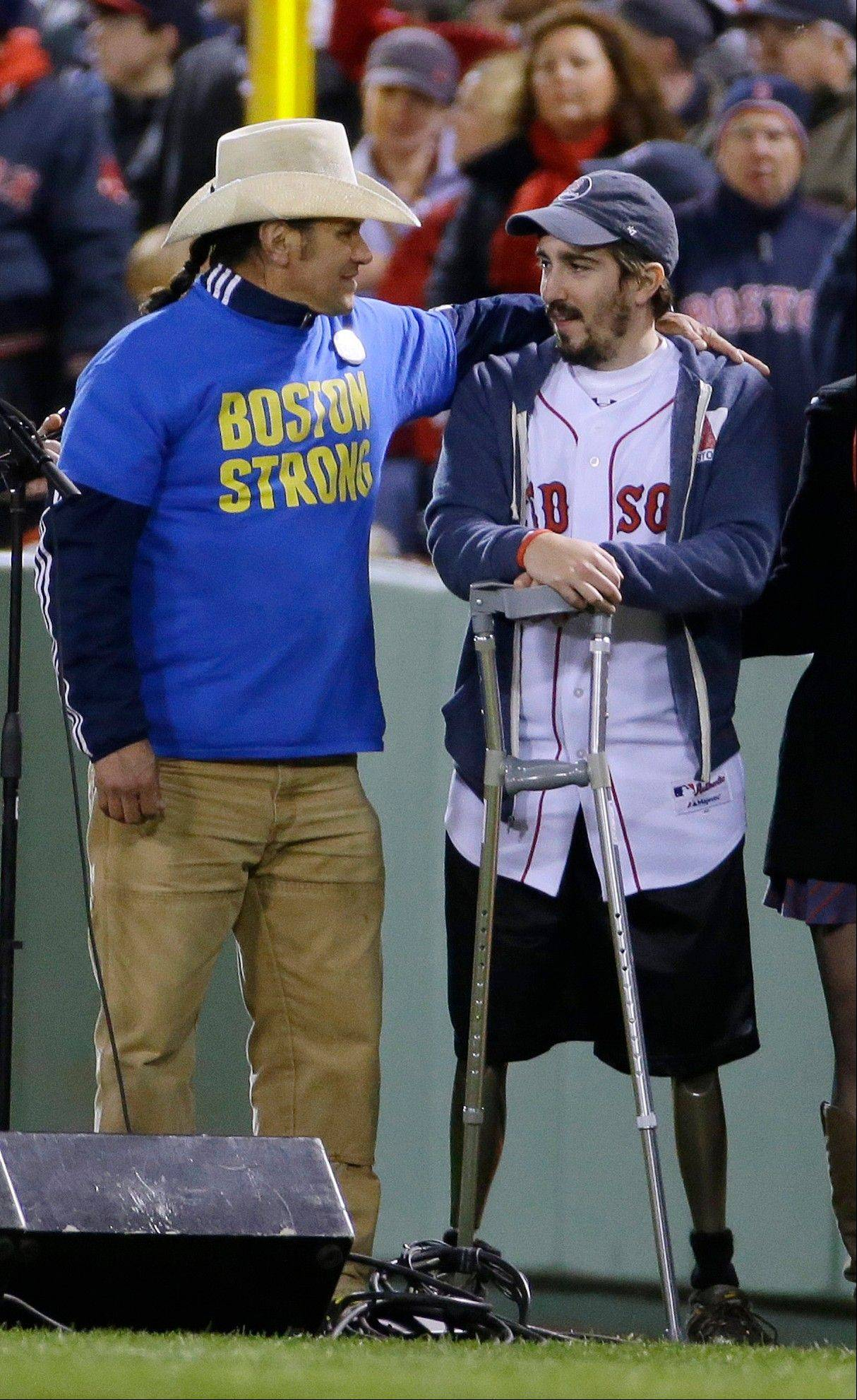 "Carlos Arredondo, left, puts his arm around Boston Marathon bombing survivor Jeff Bauman, as James Taylor, unseen, performs ""God Bless America"" during the seventh\-inning stretch of Game 2."