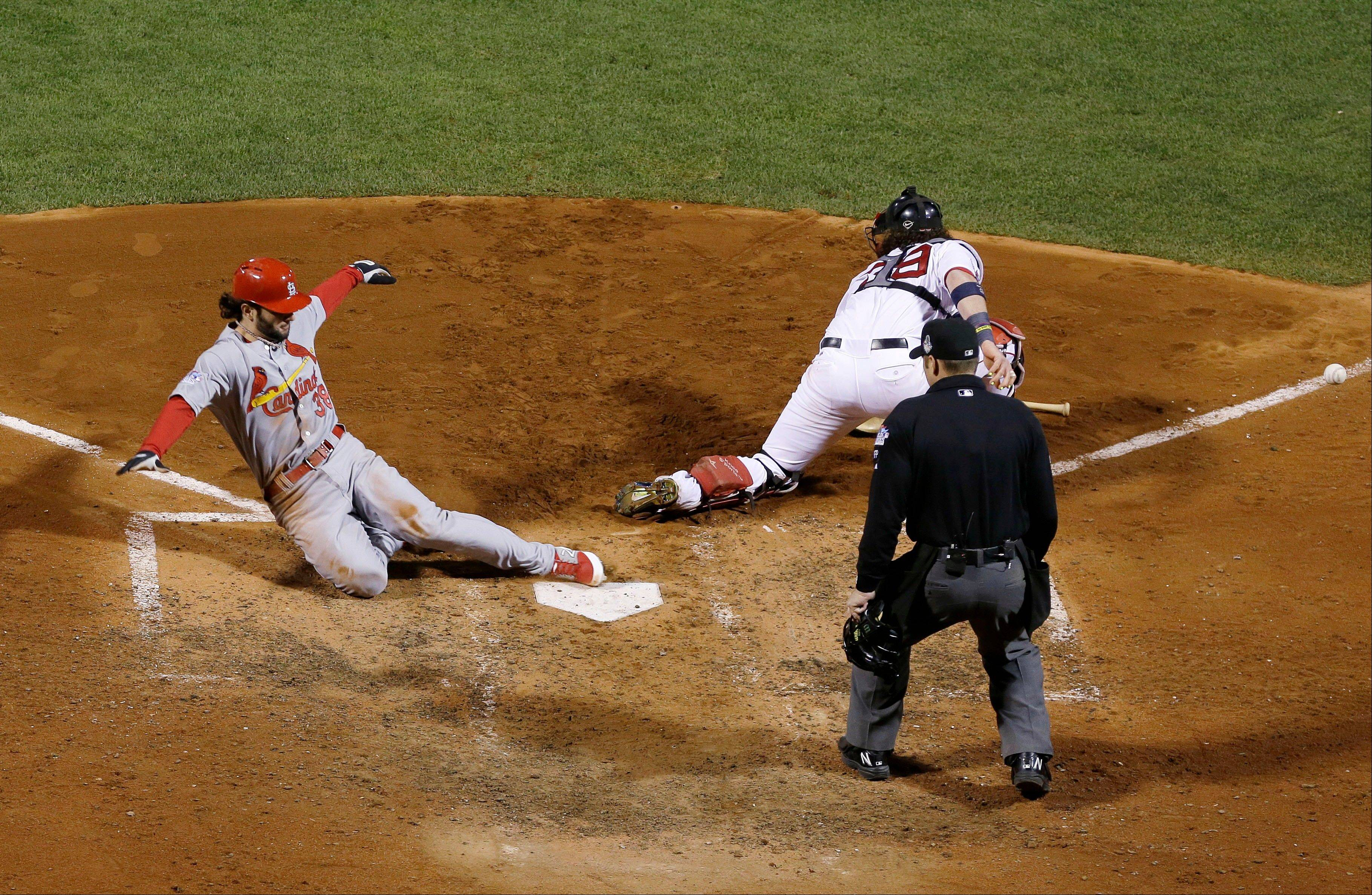 The Cardinals' Pete Kozma scores on a sacrifice fly as Red Sox catcher Jarrod Saltalamacchia has trouble with the throw during the seventh inning.