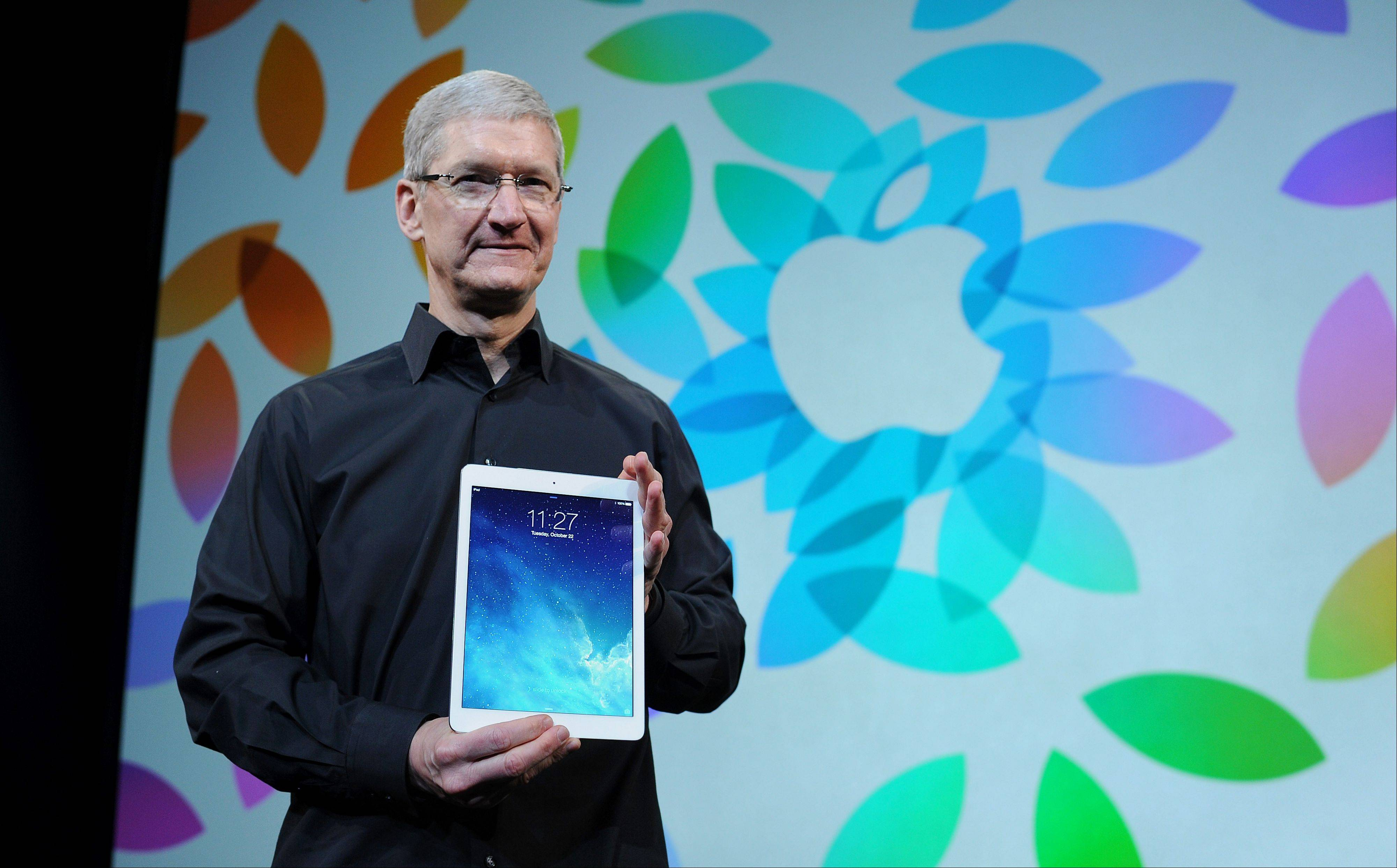 Tim Cook, chief executive officer of Apple Inc., displays the iPad Air during a press event at the Yerba Buena Center in San Francisco. Apple Inc. introduced new iPads in time for holiday shoppers, as it battles to stay ahead of rivals in the increasingly crowded market for tablet computers.