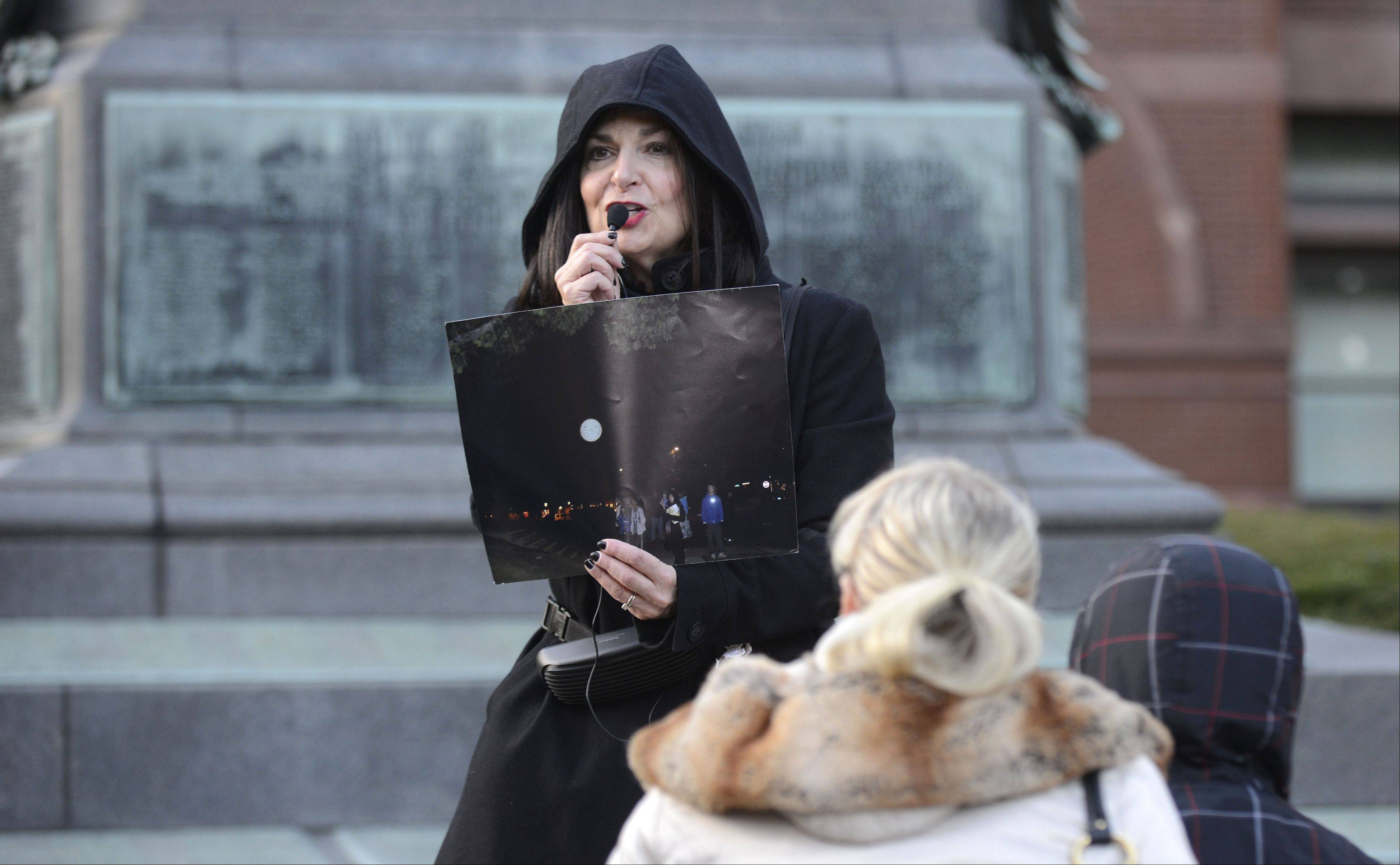Donna Latham shows a photo of an orb thought to possibly be the energy source of the ghost of the old Kane County Courthouse dubbed Clarence. She led a ghost walk through downtown Geneva Saturday hosted by the Geneva History Center.