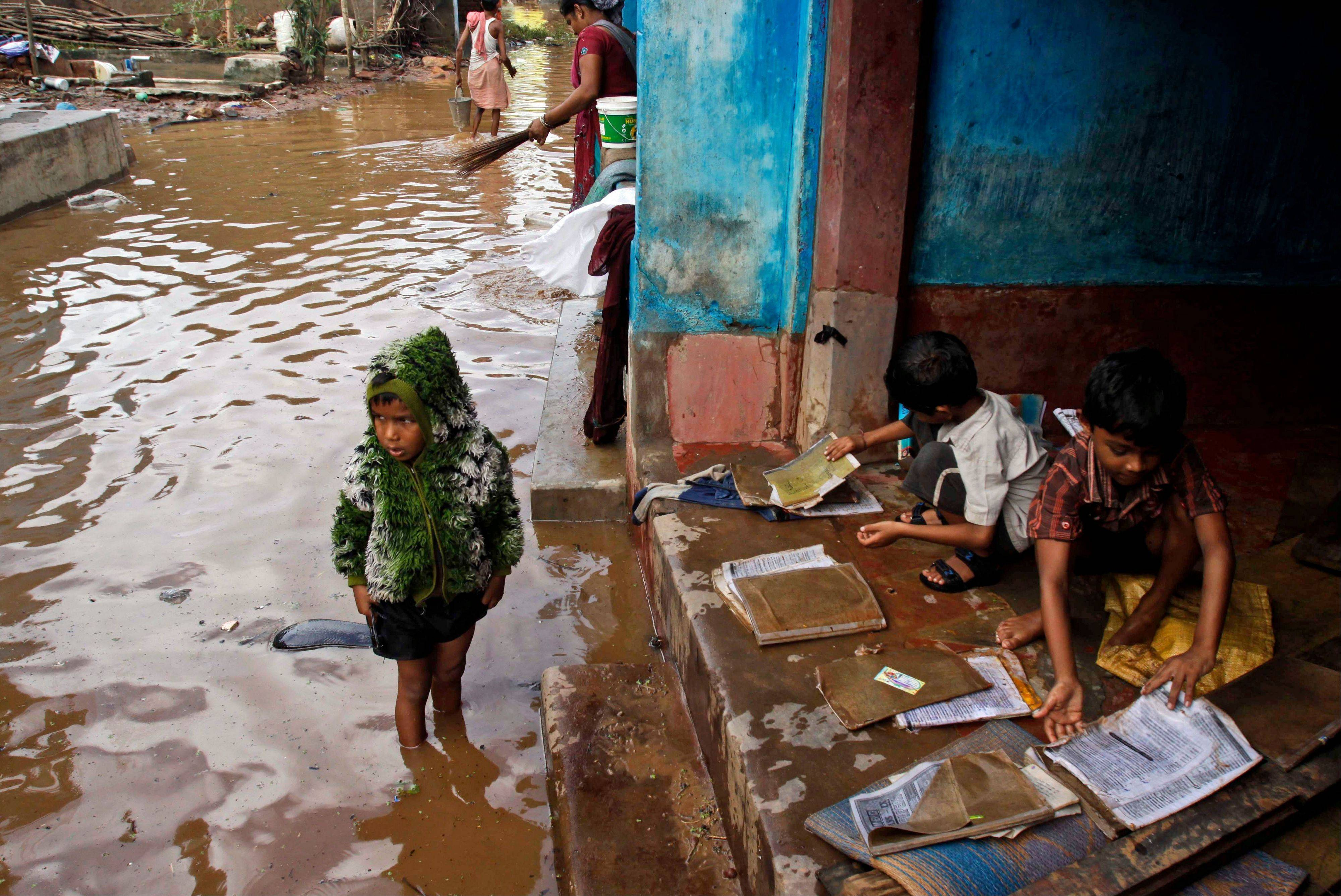 Indian village children lay out their floodwater drenched books to dry at Podapadar in Ganjam district of Orissa state, India. Days of torrential rains have unleashed floods in the states of Andhra Pradesh and Orissa.