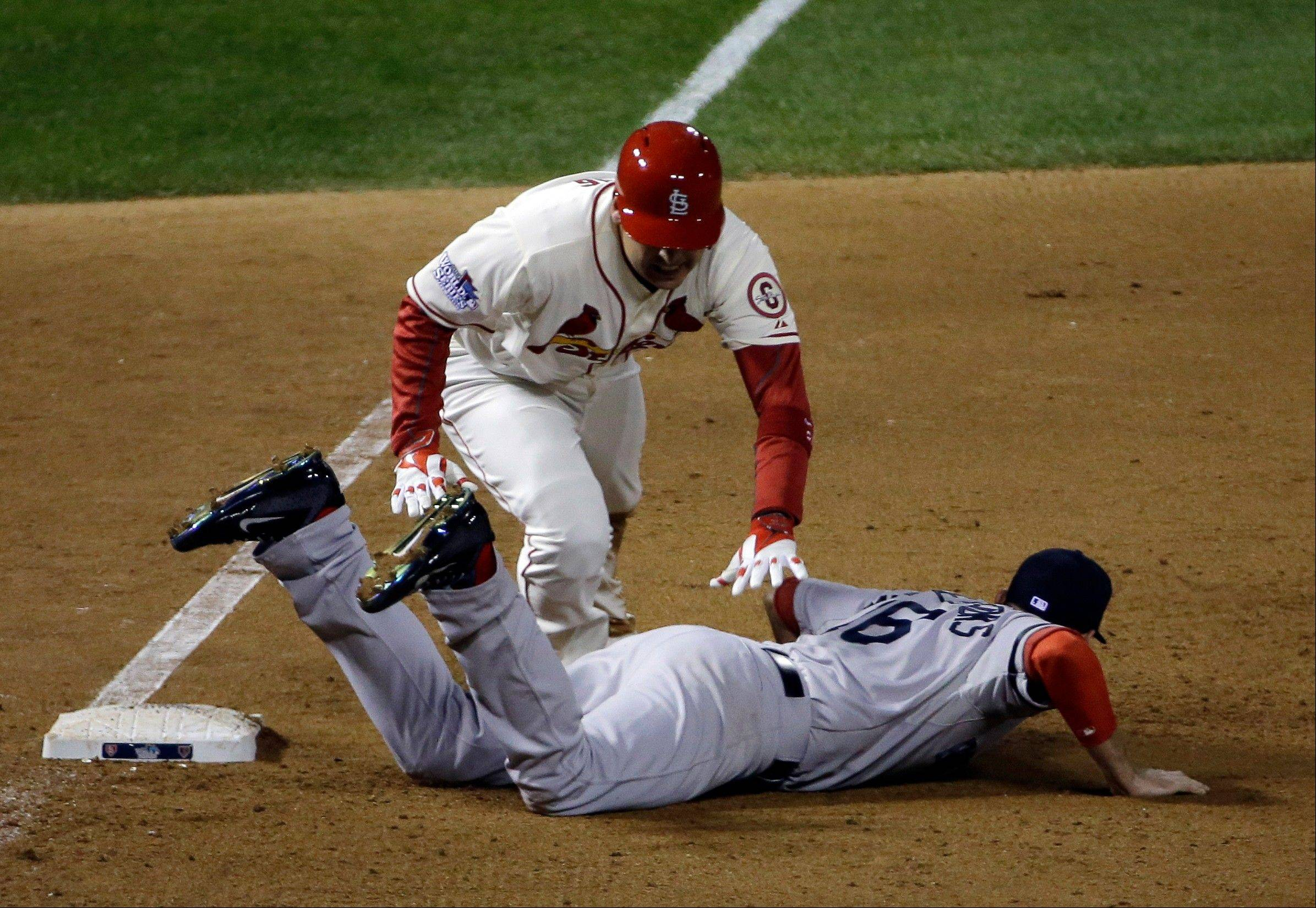 St. Louis Cardinals' Allen Craig gets tangled with the Boston Red Sox' Will Middlebrooks during the ninth inning of Game 3. Middlebrooks was called for obstruction on the play and Craig went in to score the game-winning run. The Cardinals won 5-4 to take a 2-1 lead in the series.