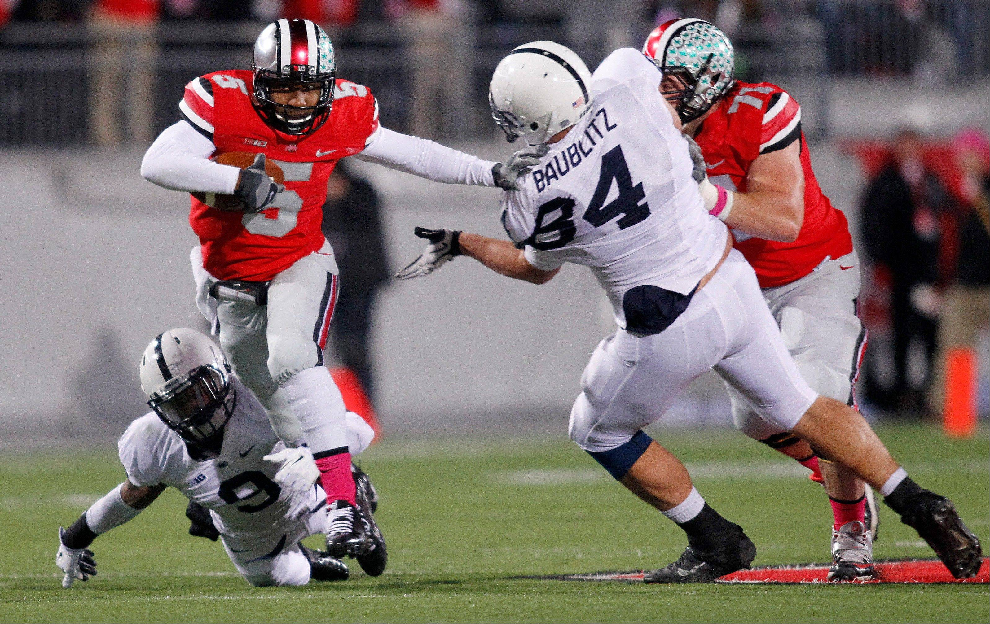 Ohio State quarterback Braxton Miller, top left, escapes the grasp of Penn State cornerback Jordan Lucas, bottom left, as Ohio State offensive lineman Corey Linsley, right, blocks Penn State defensive tackle Kyle Baublitz during the first quarter.