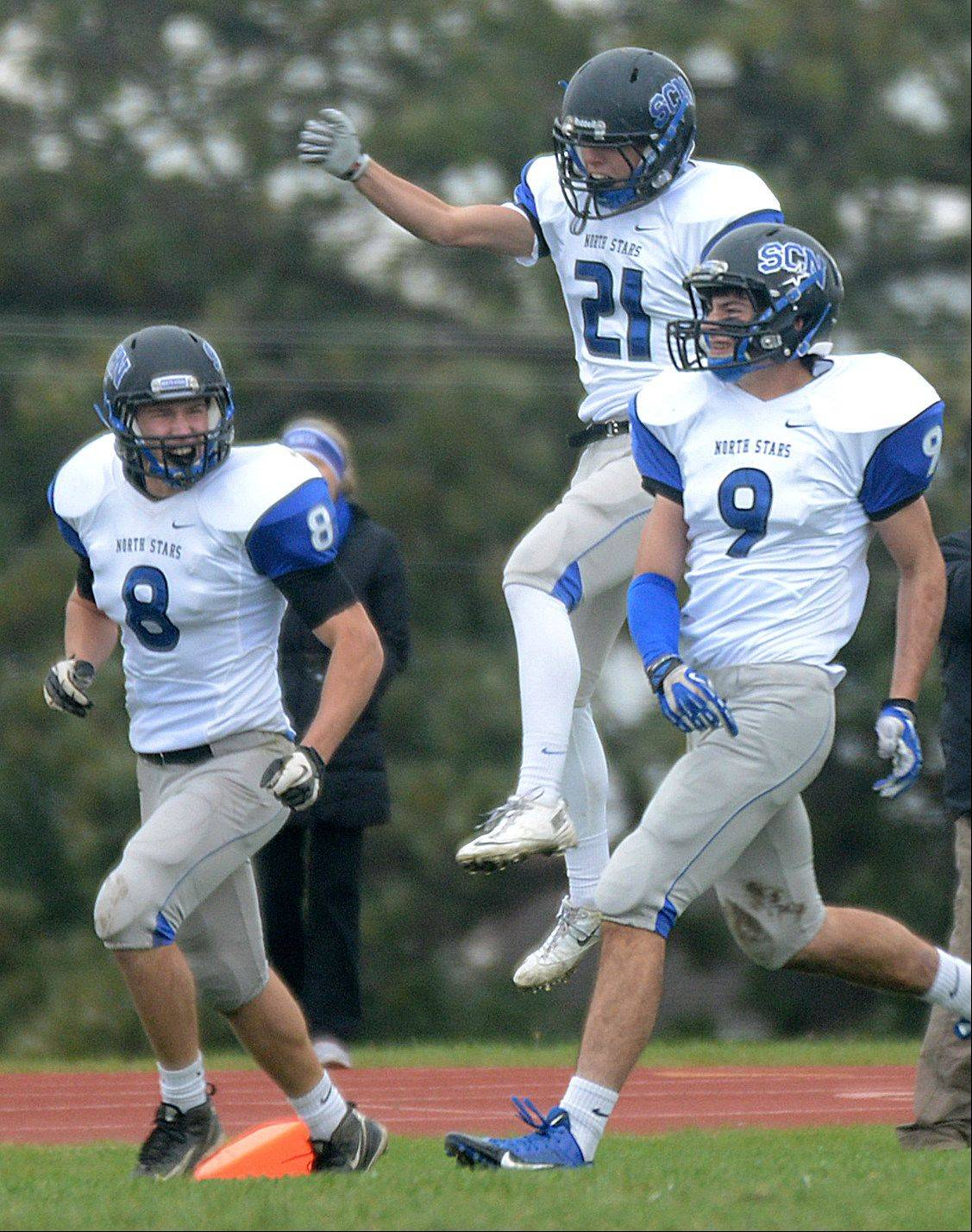 St. Charles North�s, from left, Nick Drawant, Dylan Hunter, and Cameron MacKenzie celebrate a touchdown which was scored on a South Elgin fumble in the end zone at South Elgin on Saturday.