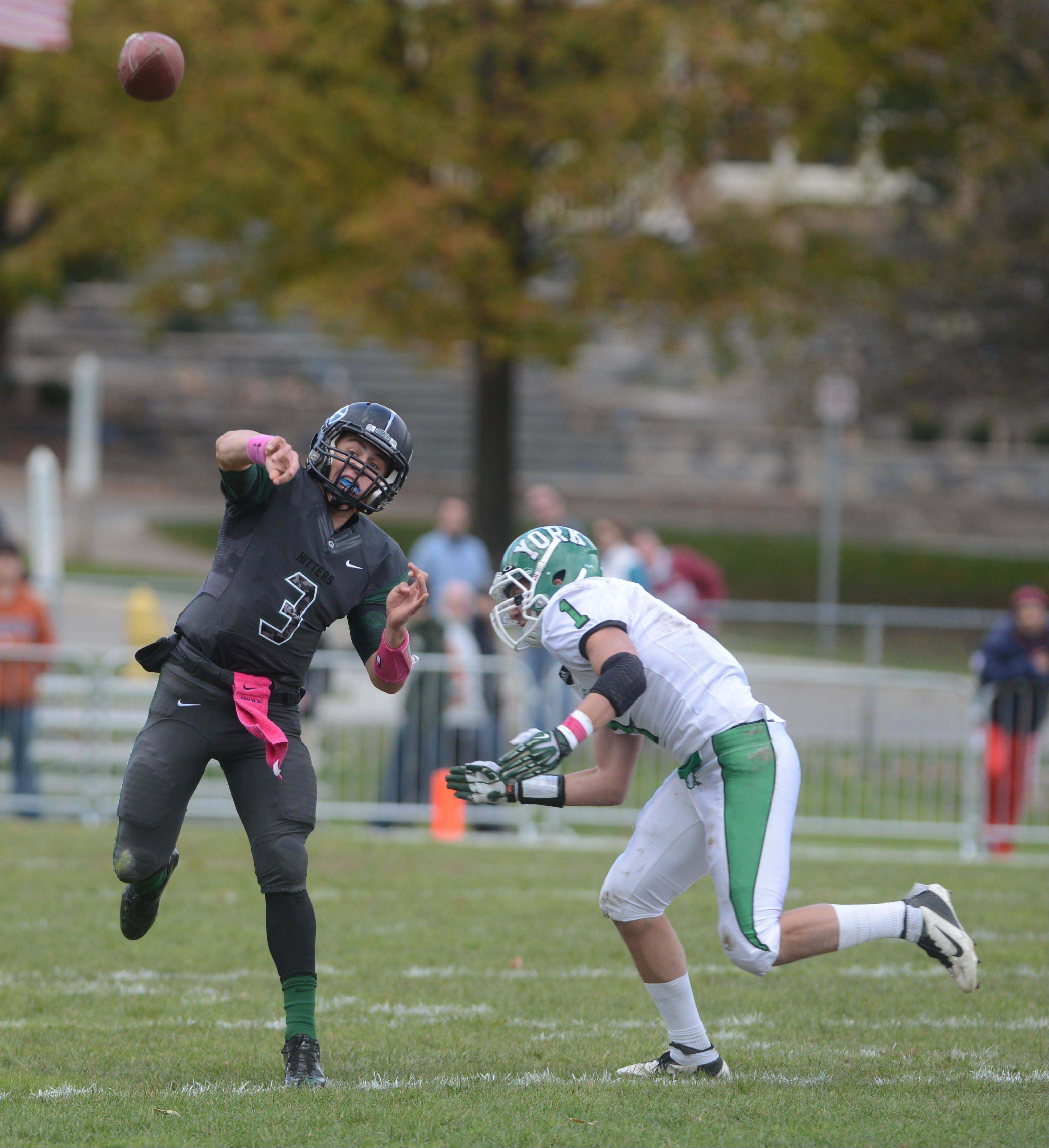 Drew Vogg of Glenbard West throws a pass as Mike Kosanovich of York cloeses in on him Saturday in Glen Ellyn.