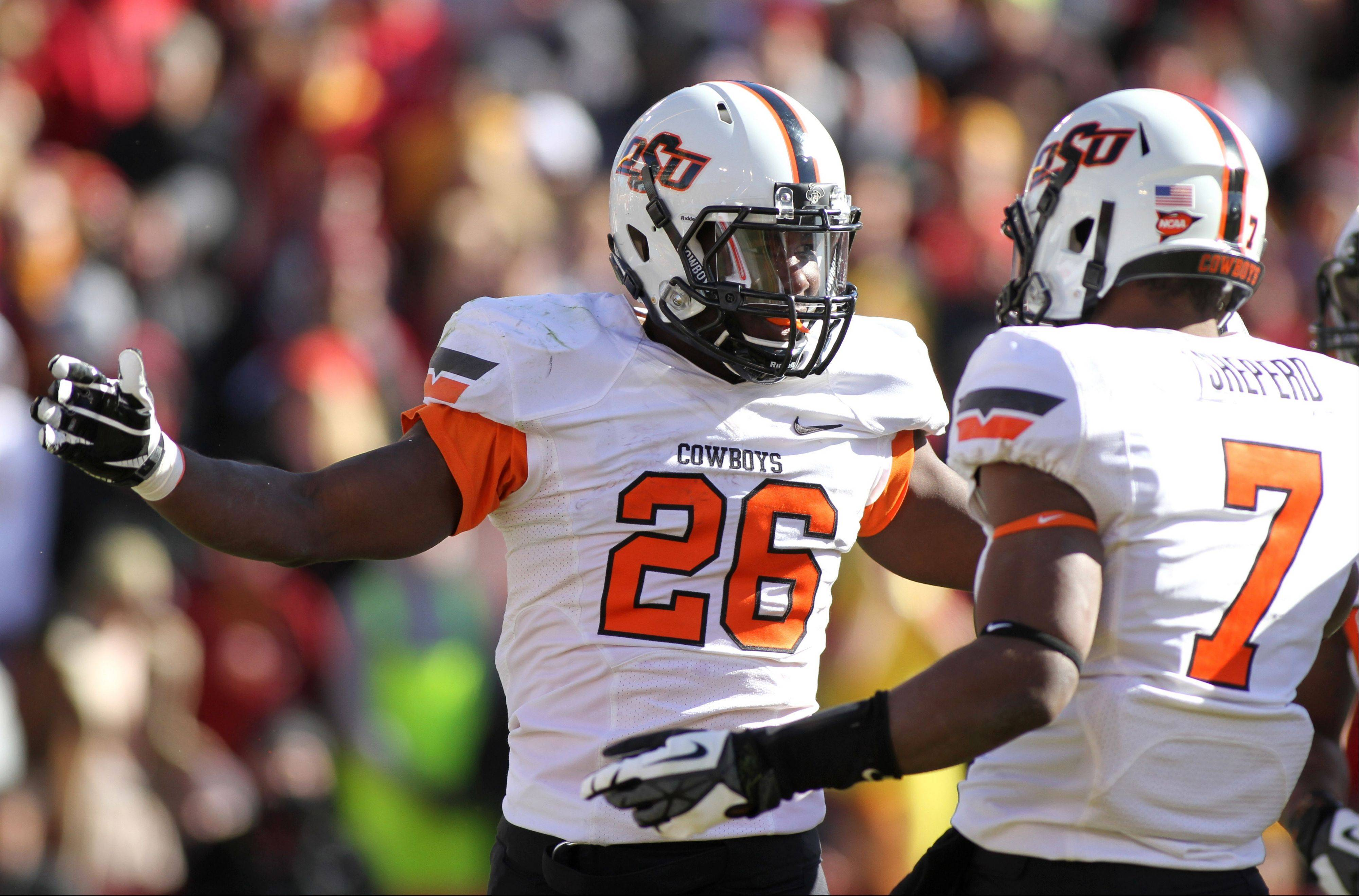 Oklahoma State running back Desmond Roland celebrates with wide receiver Brandon Sheperd after one a touchdown run in the first half. Roland rushed for 219 yards and four touchdowns in their 58-27 victory.