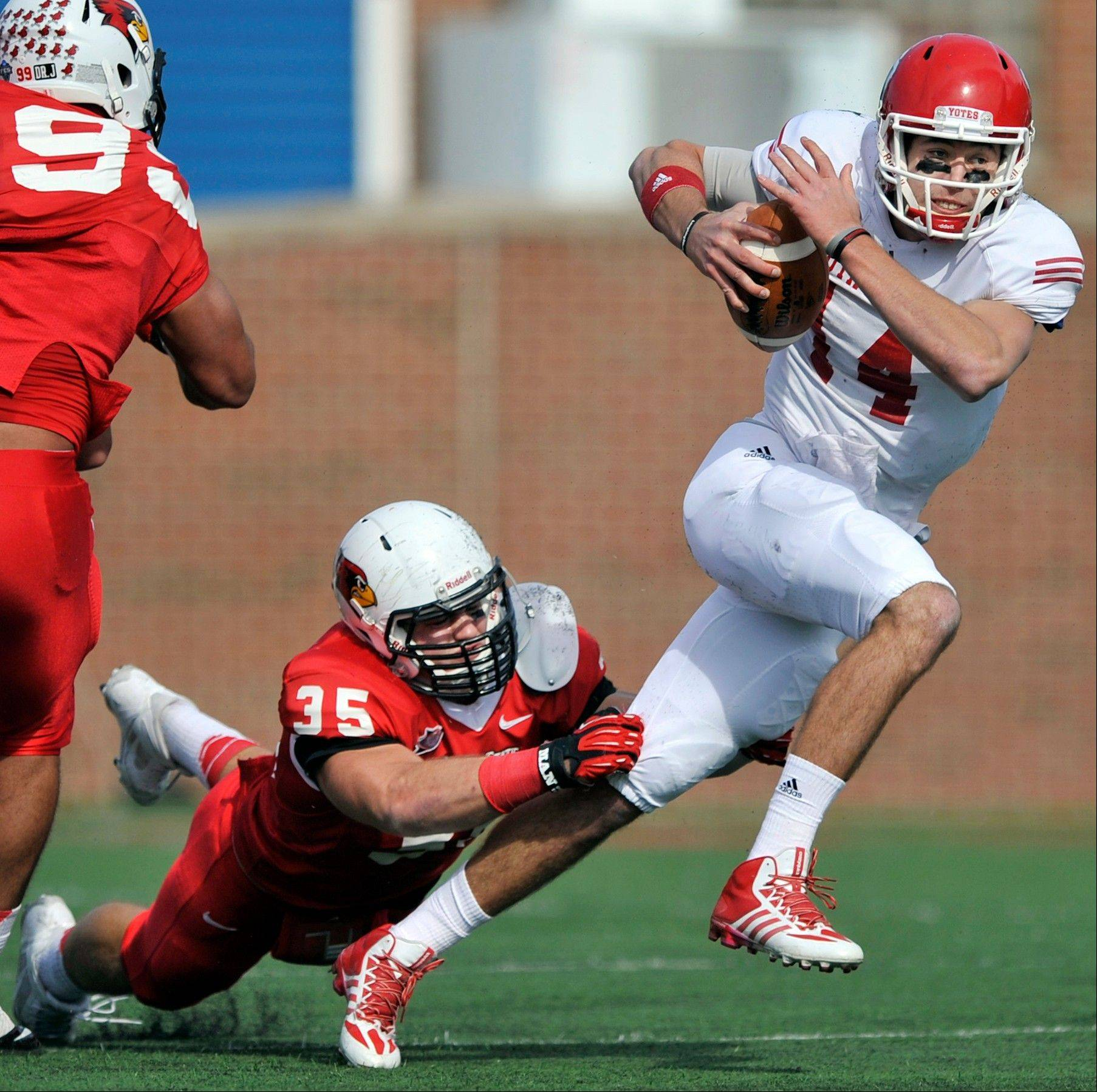 South Dakota quarterback Kevin Earl, right, breaks a tackle against Illinois State�s Colton Underwood (35), during the first half.