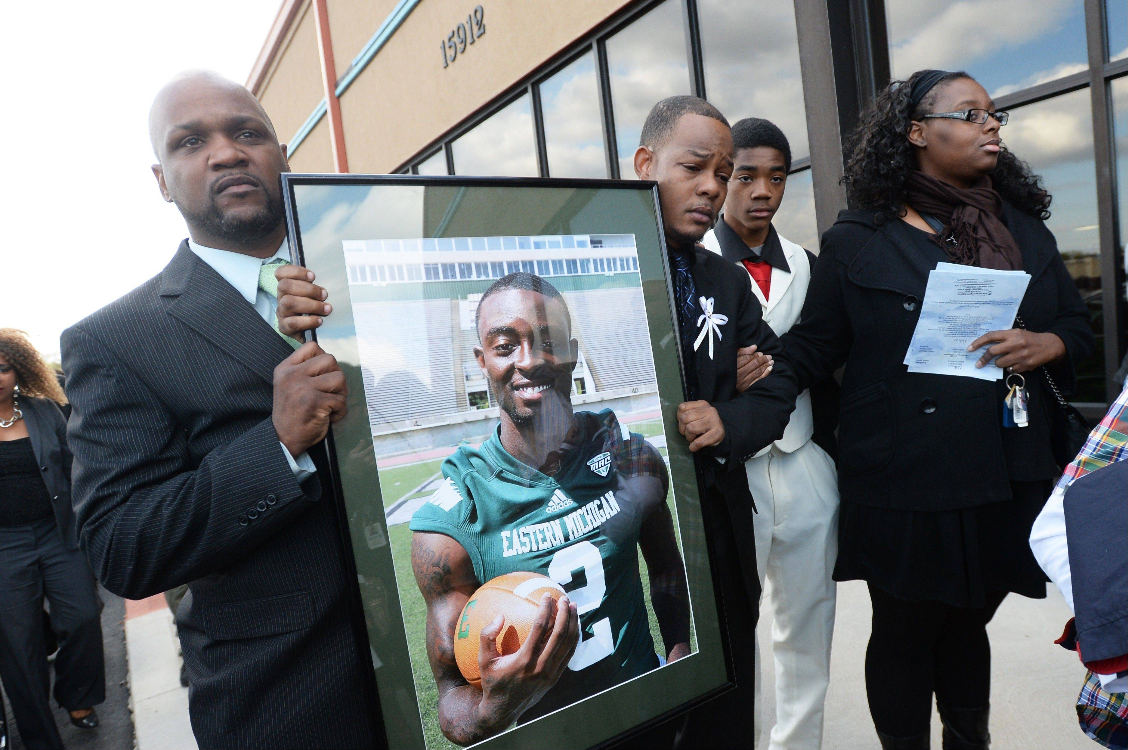 Family members Edward Harris, left, and Damien Brown, carry a framed photo of Demarius Reed, in his Eastern Michigan football jersey, as they leave Reed's funeral at Holy Temple Cathedral in Harvey, Ill., on Saturday, Oct. 26, 2013. Reed was repeatedly shot Oct. 18 in what police say may have been a robbery. (AP Photo/AnnArbor.com, Melanie Maxwell) LOCAL TV OUT; LOCAL INTERNET OUT; ONLN OUT; IONLN OUT