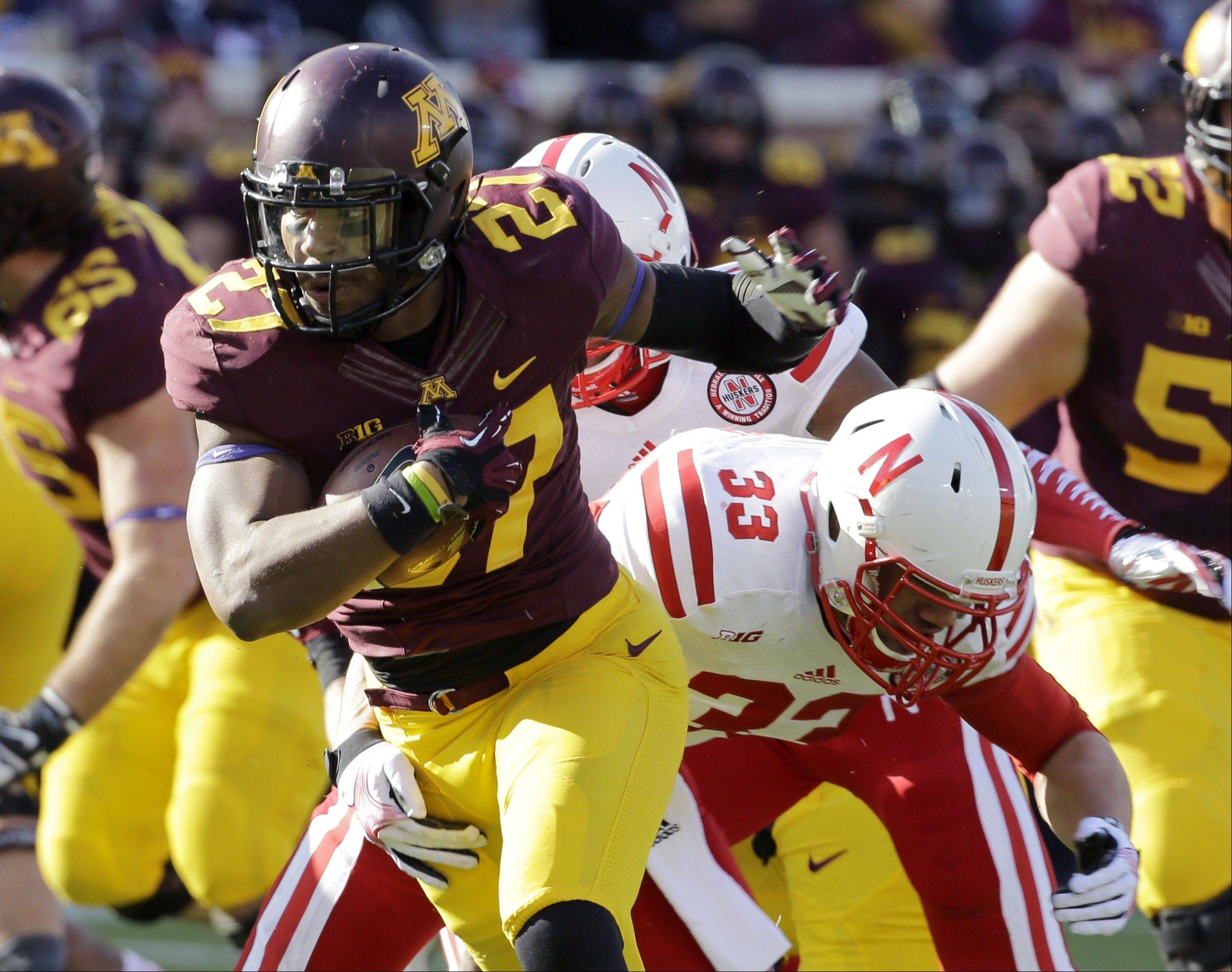 Minnesota running back David Cobb (27) evades Nebraska linebacker Jared Afalava (33) on a 7-yard gain during the first quarter of an NCAA college football game in Minneapolis Saturday, Oct. 26, 2013. (AP Photo/Ann Heisenfelt)