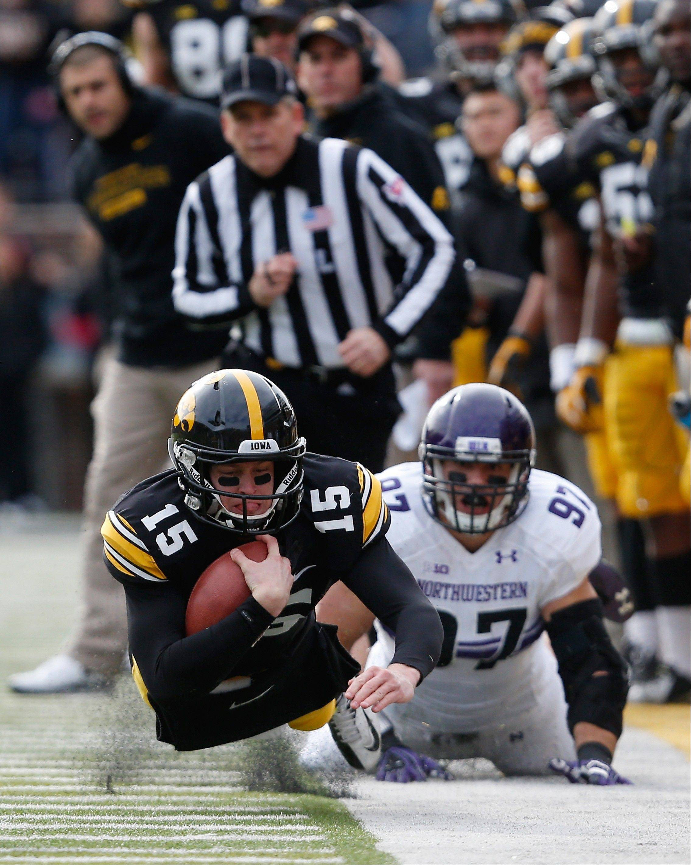 Iowa quarterback Jake Rudock (15) dives for a first down in front of Northwestern's Tyler Scott (97).