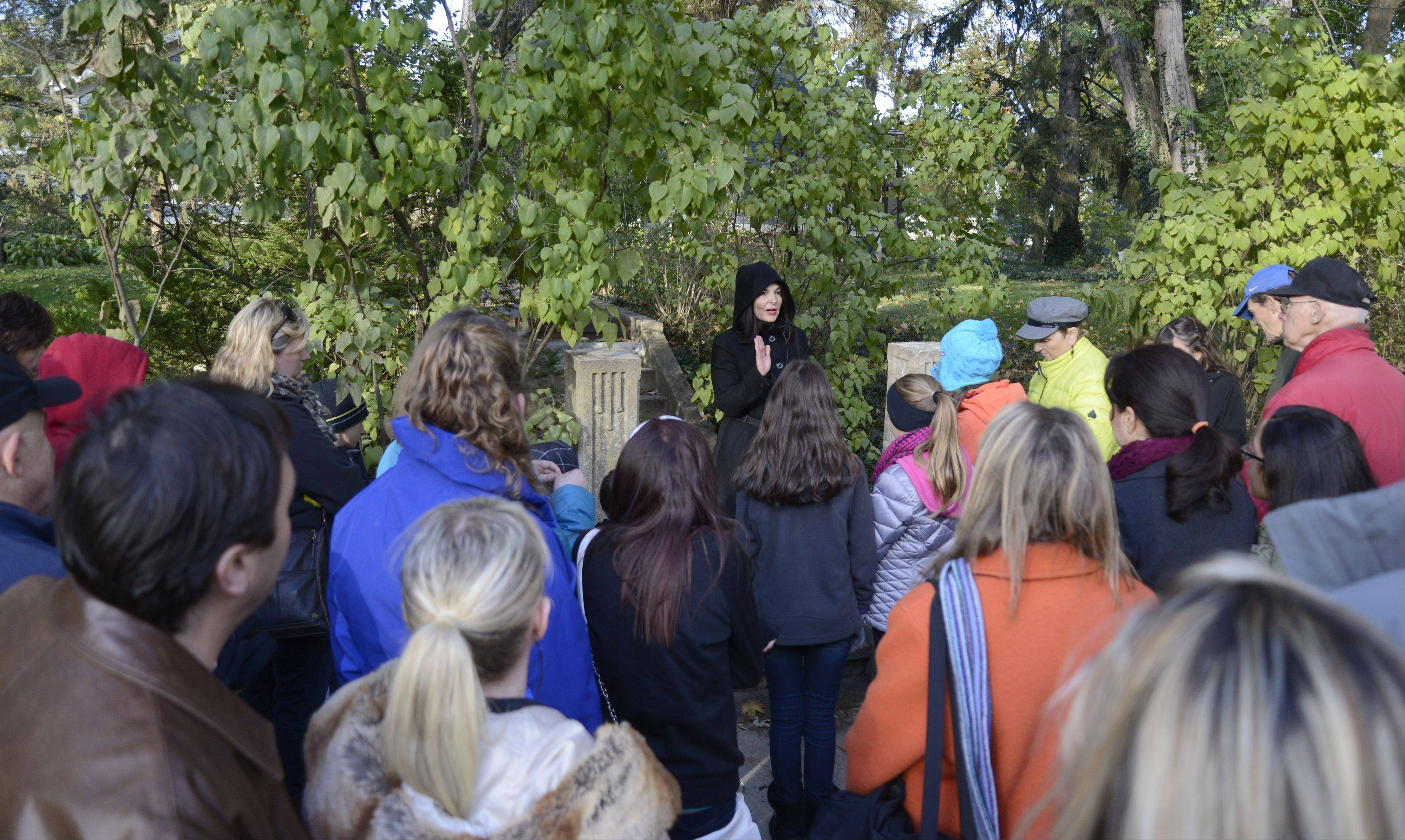"Donna Latham, author of ""Ghost of the Fox River Valley"" and resident of Batavia, talks about the 1936 cold case murder of Geneva resident Nella Panunzi while leading a ghost walk through downtown Geneva on Saturday."