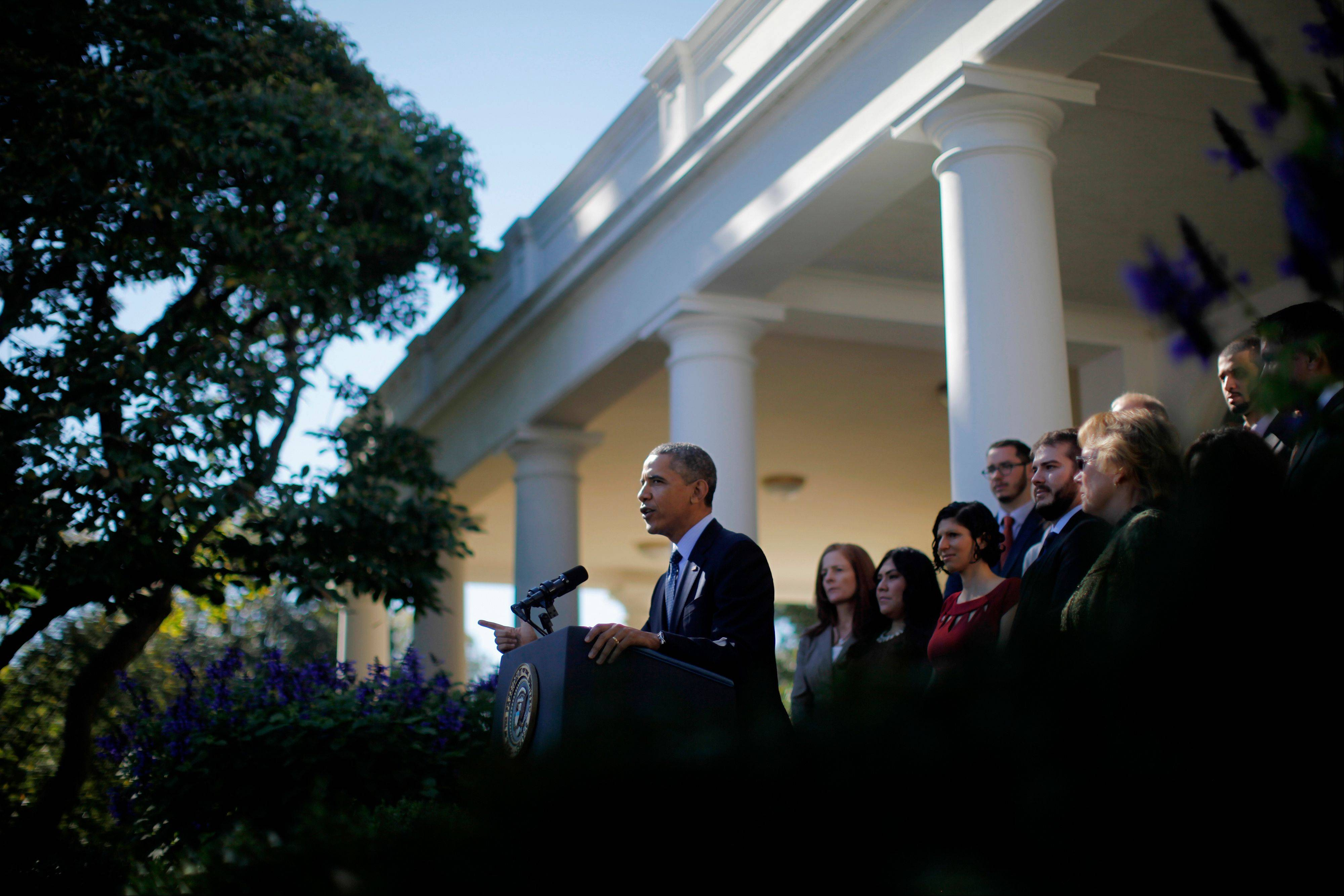 President Barack Obama, standing with supporters of his health care law, speaks Monday in the White House Rose Garden in Washington about the problem ridden rollout of his health care overhaul.