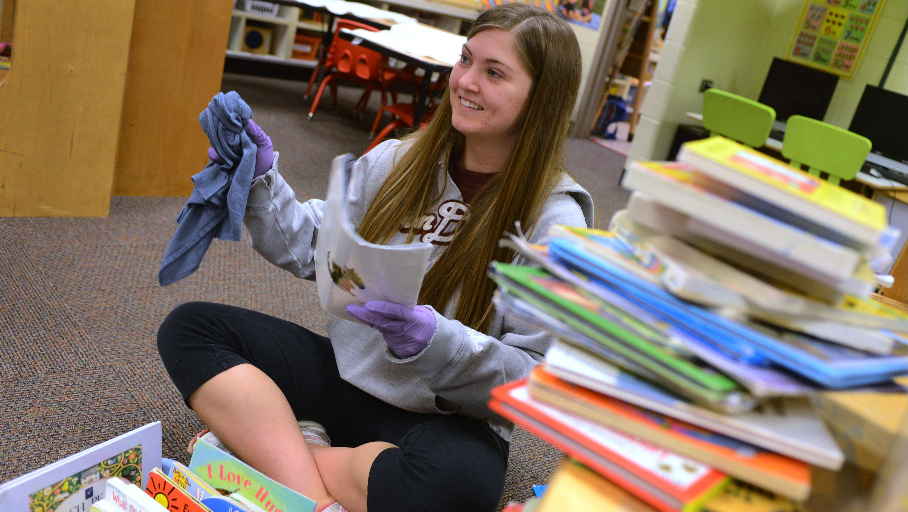 Antioch resident Katie Graziano wipes down books in the College of Lake County Children's Learning Center Saturday.