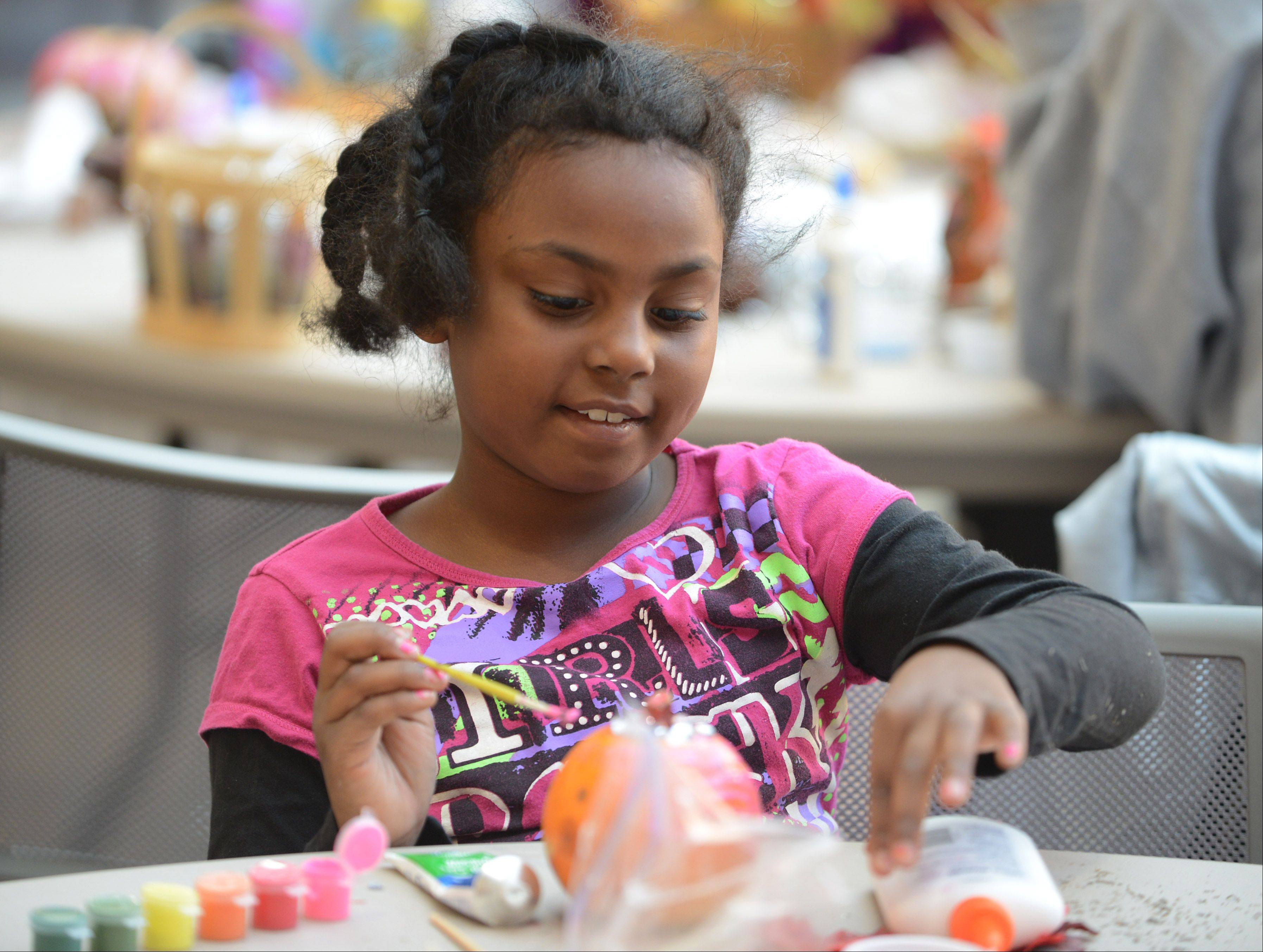Madison Booker, 7, of Round Lake Beach helped make craft items for the College of Lake County Women's Center during Saturday's Make a Difference Day at the college in Grayslake.