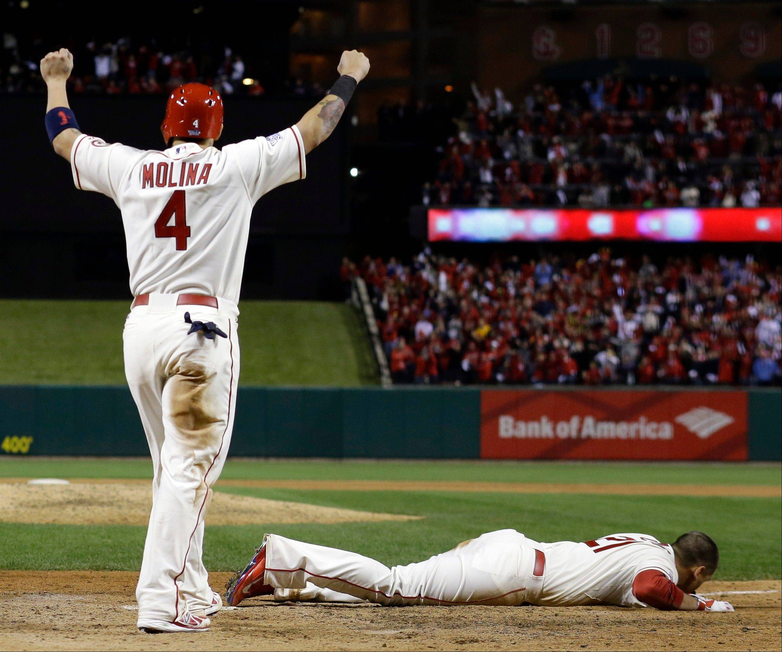 St. Louis Cardinals' Yadier Molina reacts as Allen Craig lies on home plate after getting tangled with Boston Red Sox's Will Middlebrooks during the ninth inning.