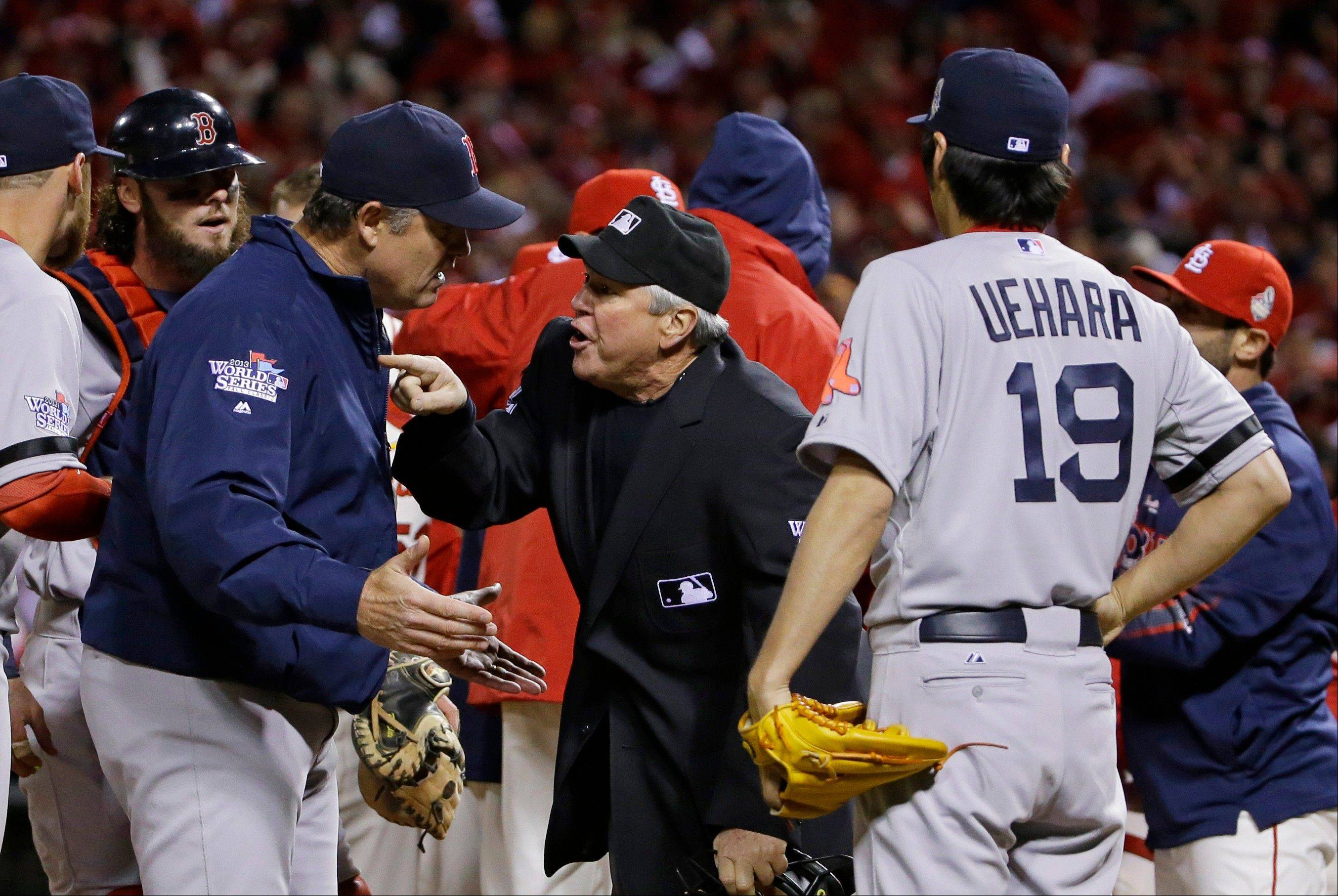 Boston Red Sox manager John Farrell argues with home plate umpire Dana DeMuth after St. Louis Cardinals scored the winning run on an obstruction play during the ninth inning.