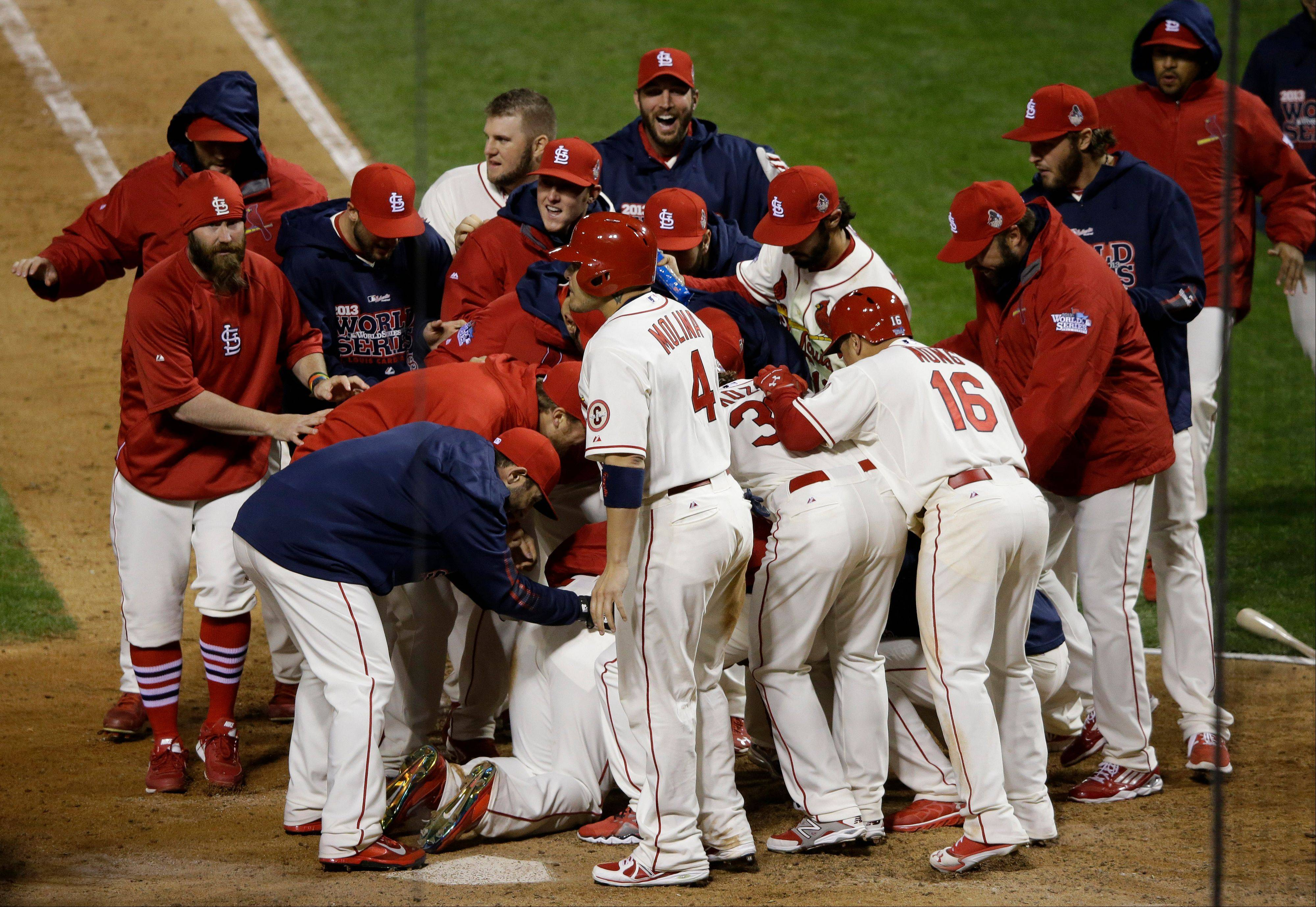 St. Louis Cardinals players celebrate with Allen Craig, on ground, after Craig scored the game-winning run on an obstruction play in the ninth inning.