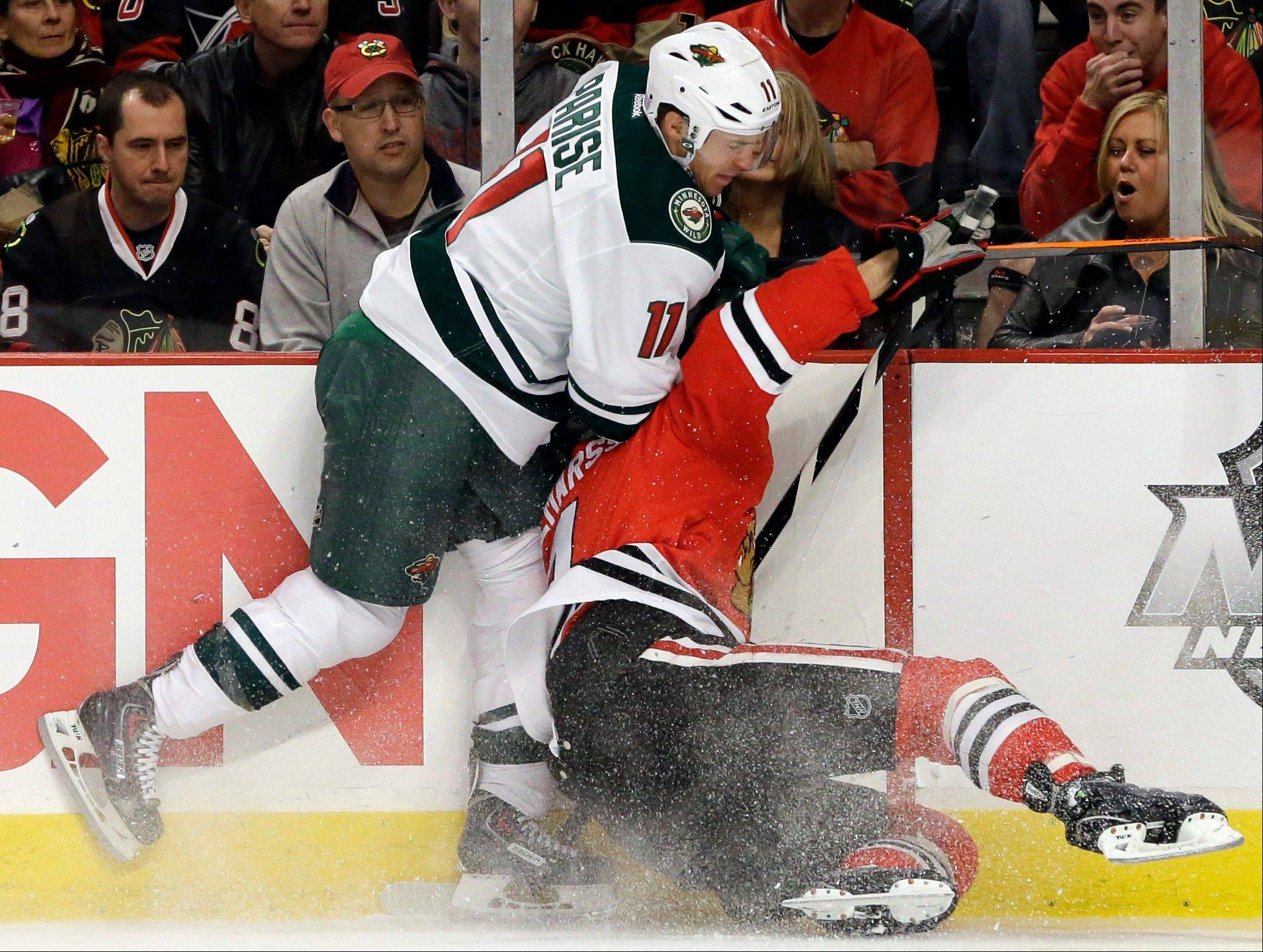 The Blackhawks' Niklas Hjalmarsson (4), right, is checked by Minnesota Wild's Zach Parise (11) during the first period.