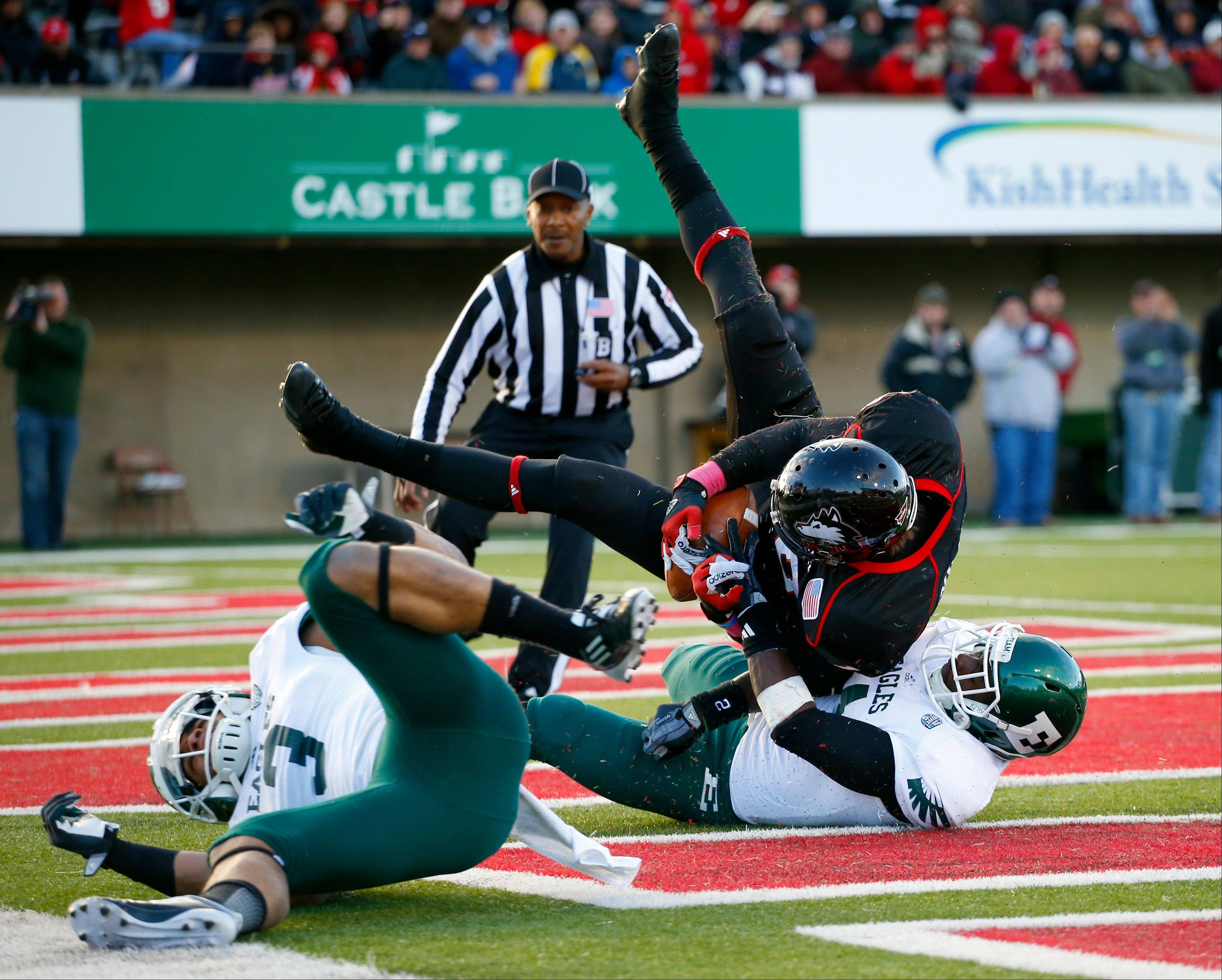 Northern Illinois linebacker Bobby Jones IV, center, rolls over Eastern Michigan defensive back Willie Creear, right, as teammate Donald Coleman, left, rolls away during the second half.