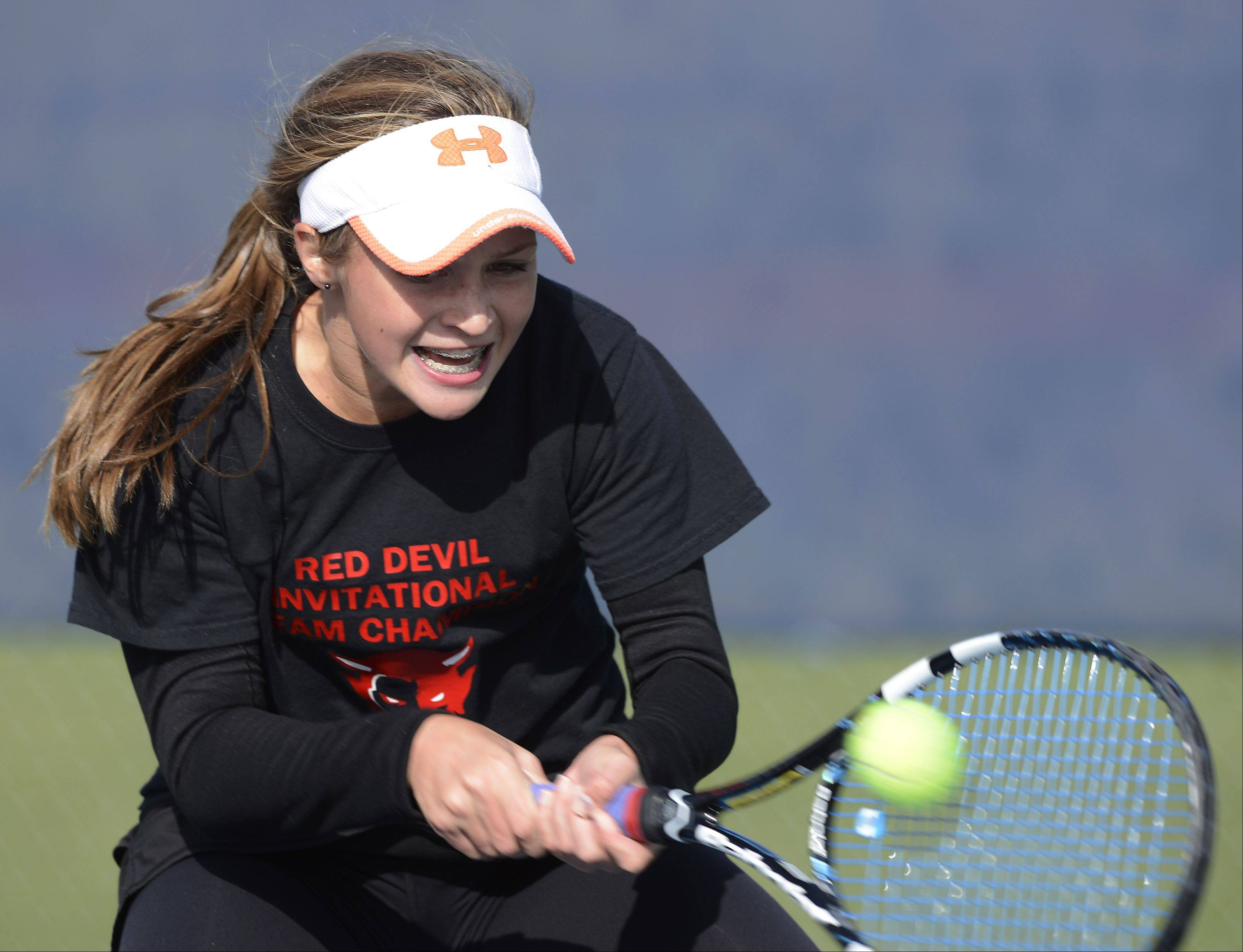 Hinsdale Central's Isabelle Lorenzini returns a volley during the girls state tennis semifinals at Buffalo Grove High School Saturday.