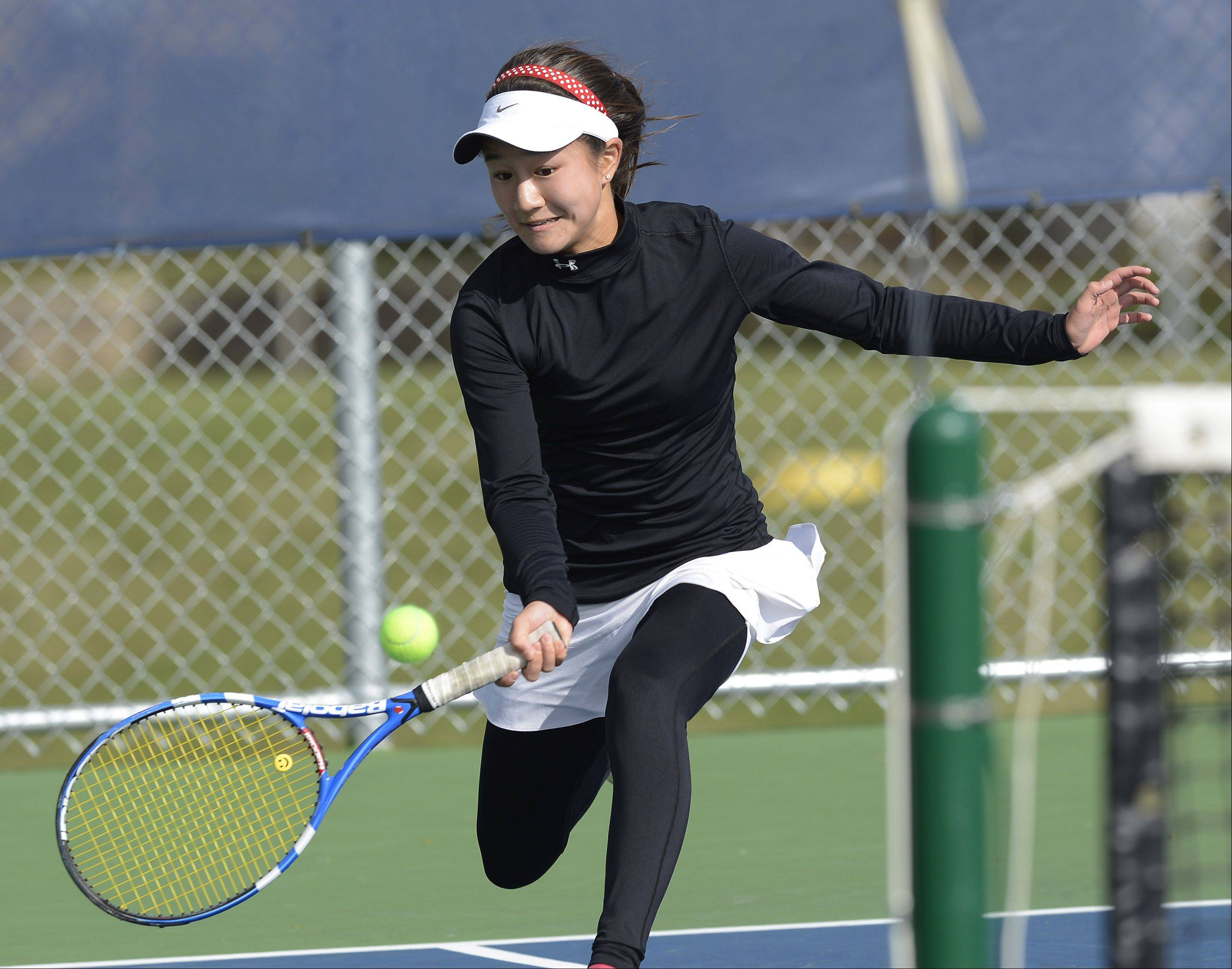 Naperville Central's Tiffany Chen hustles to keep a ball in play during the girls state tennis semifinals at Buffalo Grove High School Saturday.