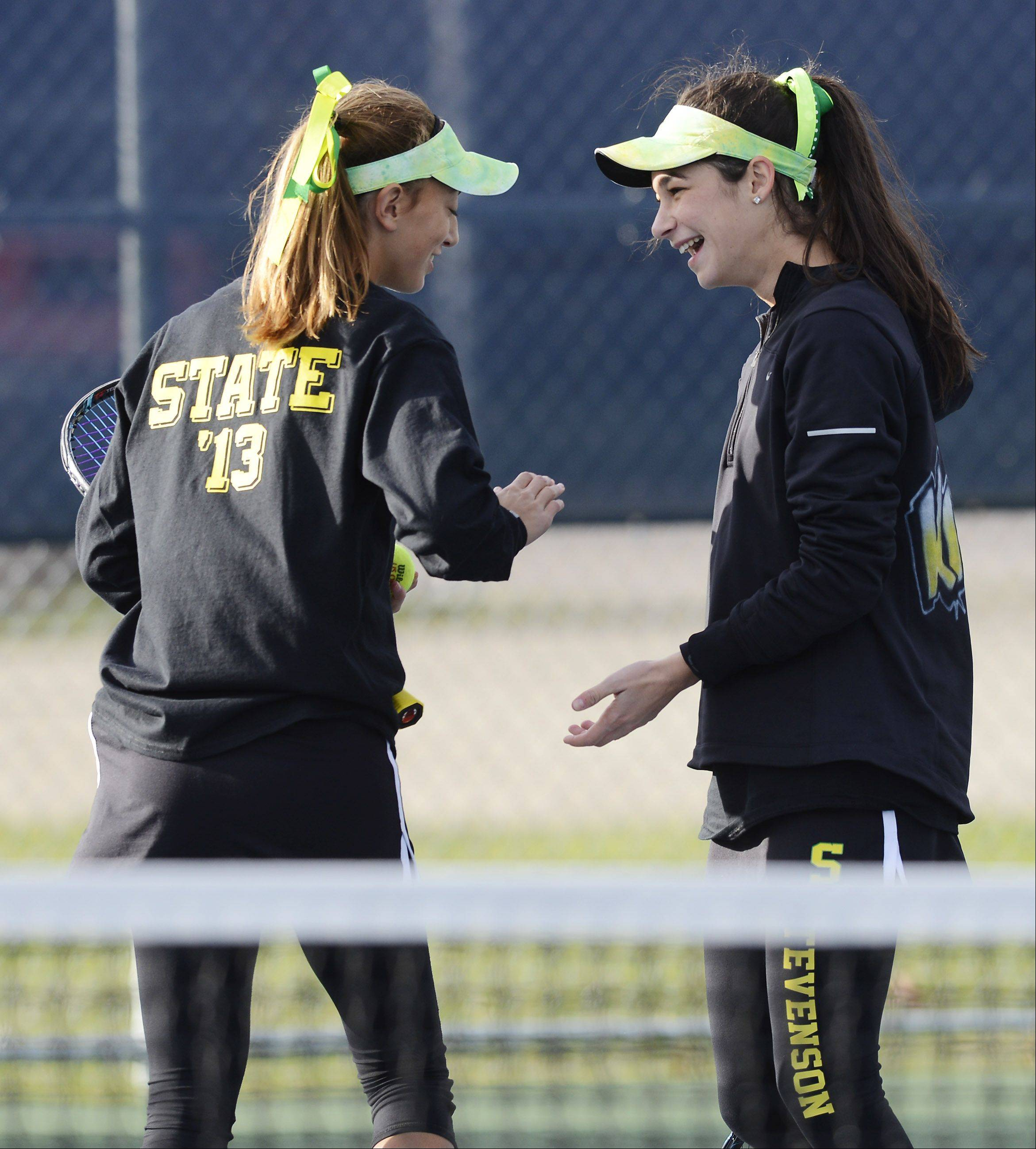 Stevenson doubles players Alexxis Kiven, left, and Kendall Kirsch smile with one another during the girls state tennis semifinals at Buffalo Grove High School Saturday.