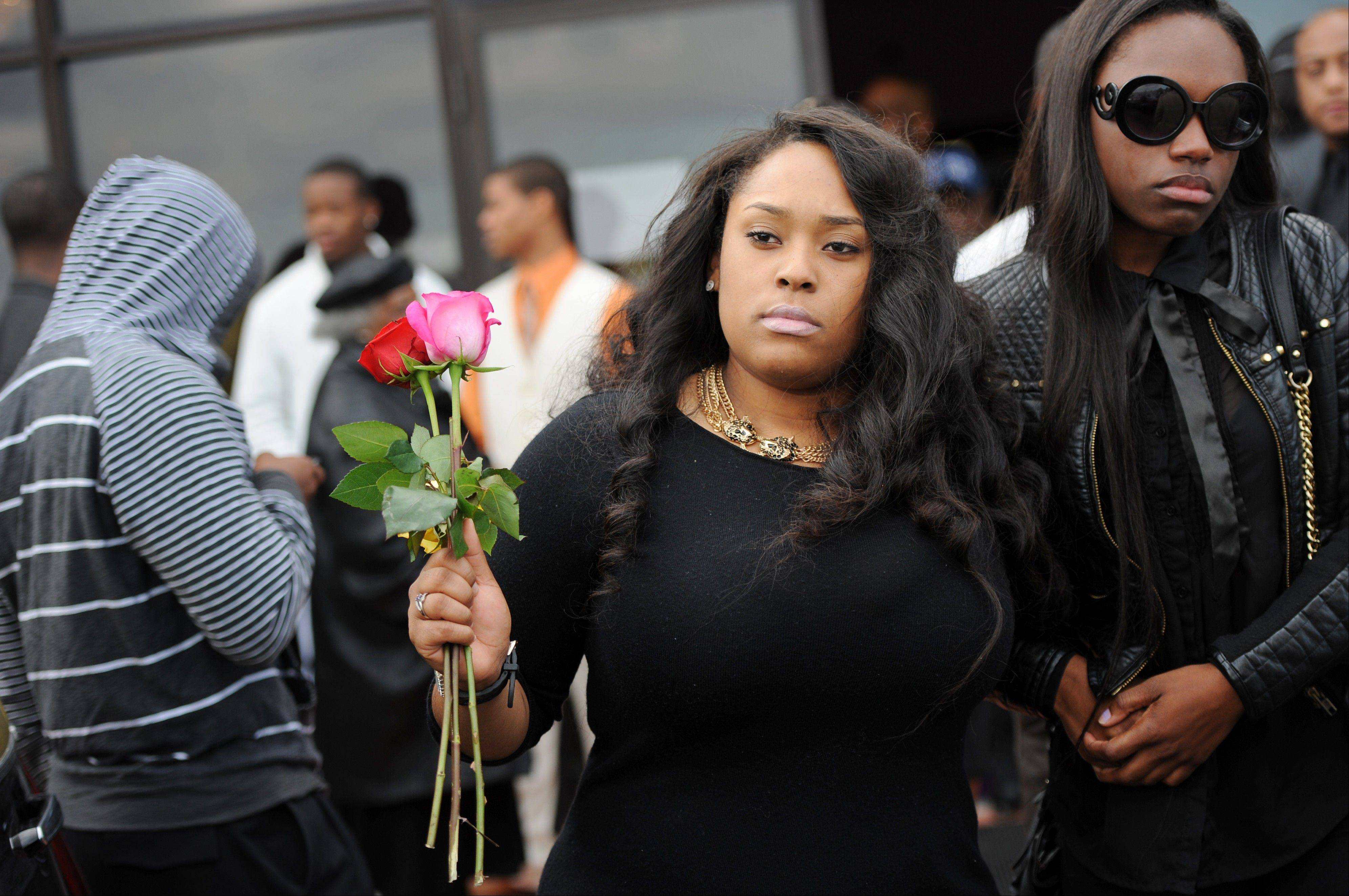 A mourner holds two roses as she walks out of the funeral for Eastern Michigan football player and Chicago native Demarius Reed at Holy Temple Cathedral in Harvey, Ill., on Saturday, Oct. 26, 2013. Reed was repeatedly shot Oct. 18 in what police say may have been a robbery. (AP Photo/AnnArbor.com, Melanie Maxwell) LOCAL TV OUT; LOCAL INTERNET OUT; ONLN OUT; IONLN OUT