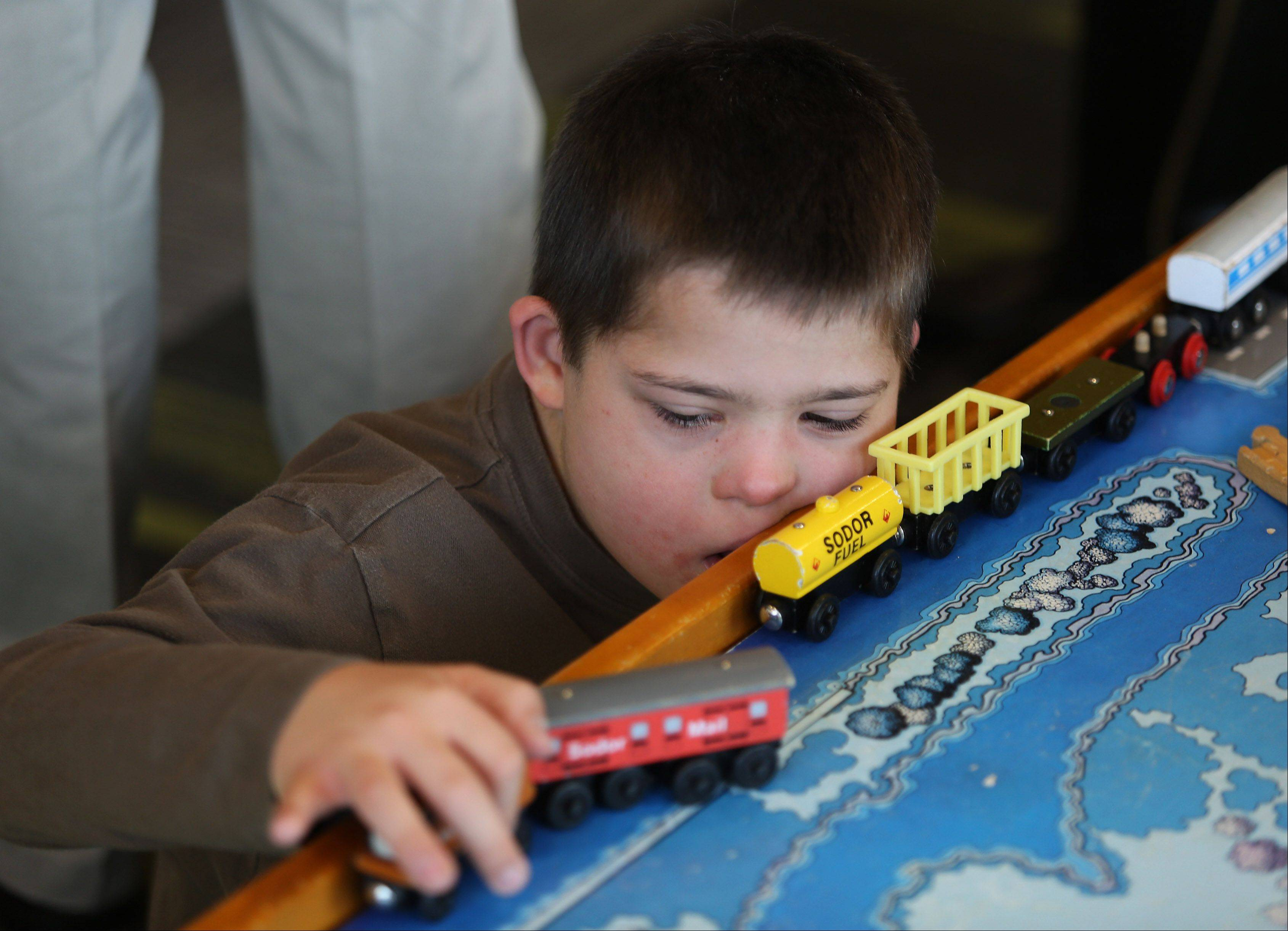 Caleb Tameling, 8, of Lombard plays with a train set Sunday during the grand opening of GiGi's Playhouse National Achievement Center in Hoffman Estates. The awareness and resource center provides programs for children and adults with Down syndrome.