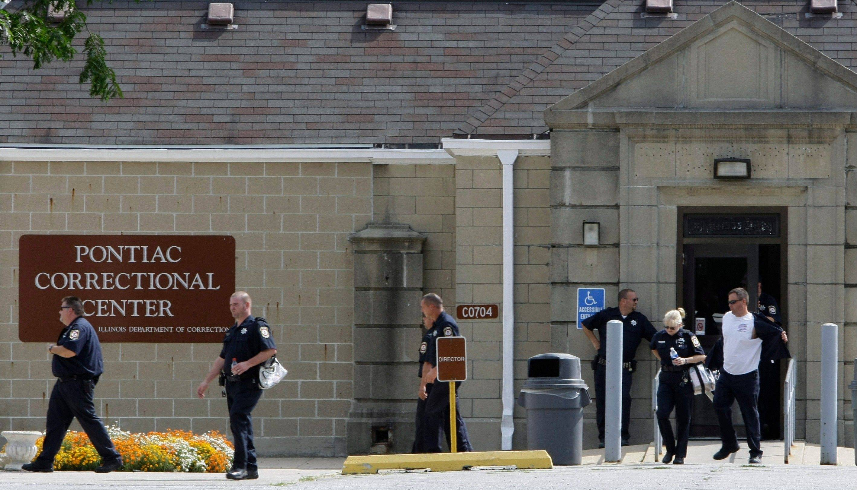 Correction officers leave the Pontiac Correctional Center in Pontiac, Ill. While top Chicago brass lobbies lawmakers to stiffen prison sentences for gun crimes — meaning more inmates in crowded prisons — The Associated Press has learned that overtime pay for those who guard those inmates jumped 34 percent last year.