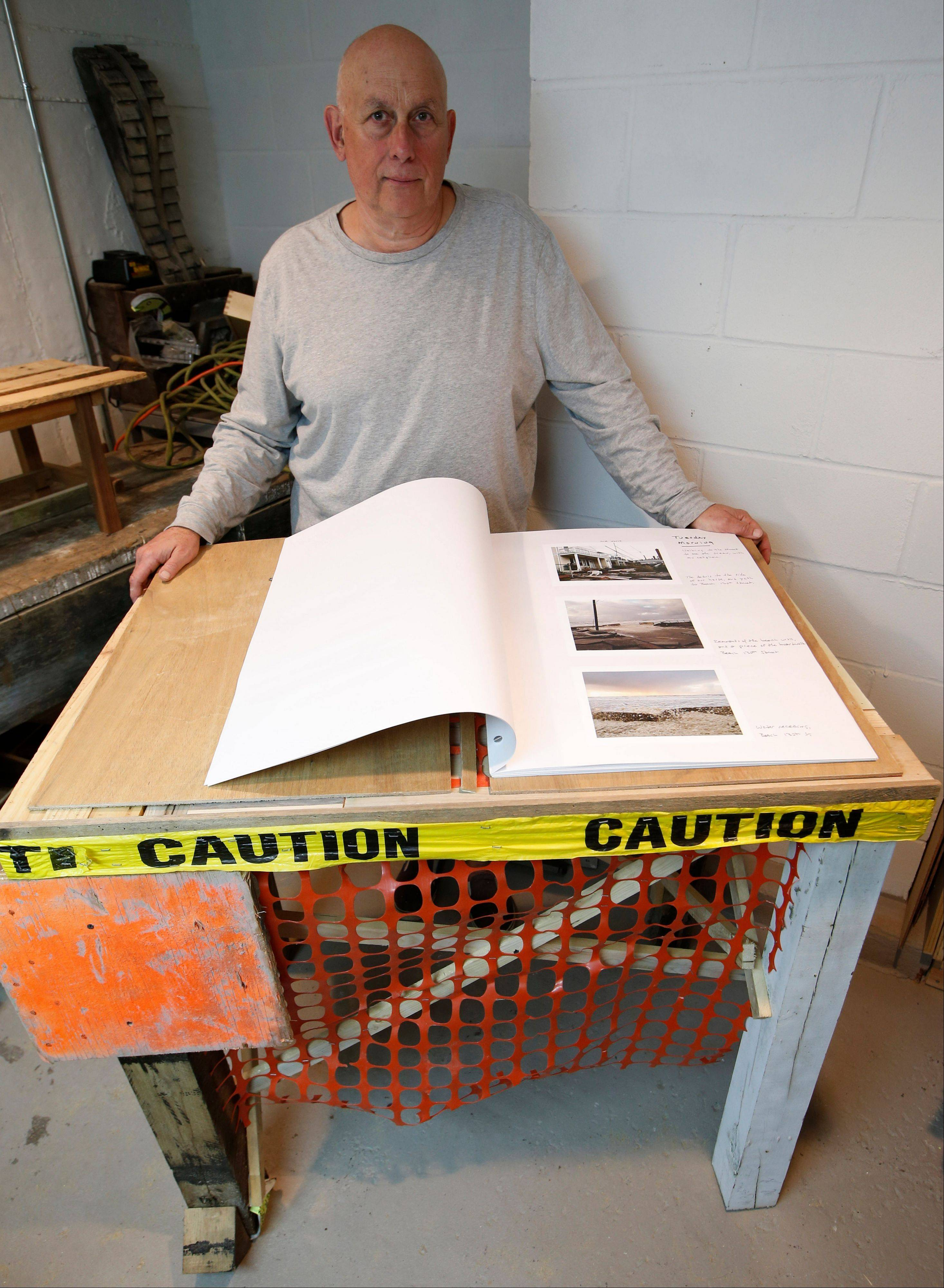 "Professional photographer Larry Racioppo created this library stand from scrap lumber, yellow ""caution"" tape and orange plastic construction fencing to display his personal photo album showing the destruction in the Belle Harbor section of the Rockaways in New York. The album is among 200 photographs on display in the exhibit ""Rising Waters: Photographs of Sandy,"" which opens at the Museum of the City of New York on Tuesday, Oct. 29, on the one-year anniversary of Sandy's destruction."