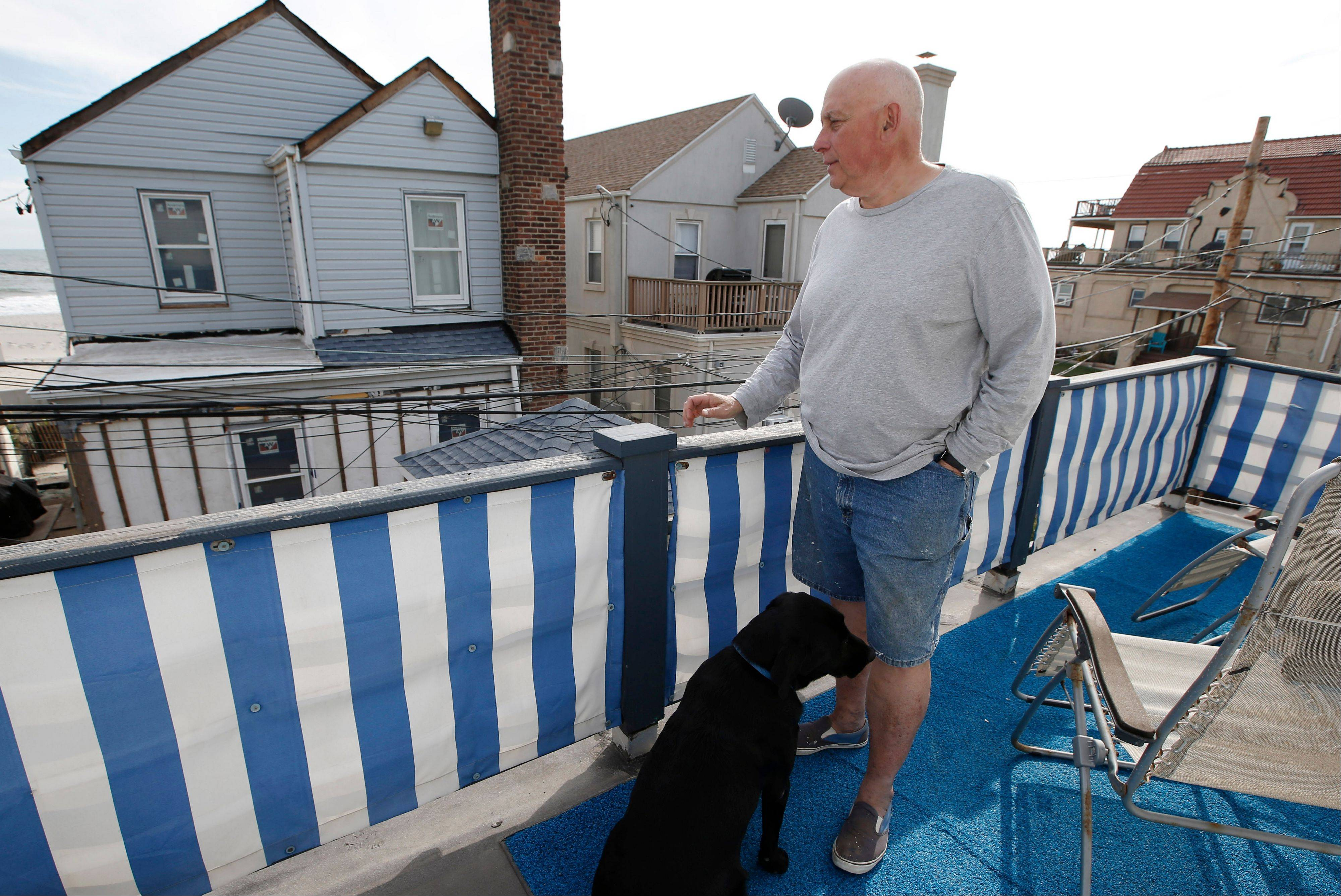Larry Racioppo, a retired staff photographer for the New York City's Housing and Preservation Department, stands on a balcony at his home just 20 feet off the ocean in the Belle Harbor section of the Rockaways in New York. Racioppo created a 22-page photo album, constructed of scrap plywood and orange plastic construction fencing, documenting his neighborhood beginning on the day of Superstorm Sandy and ending in early spring with portraits of workers repairing his flooded basement.