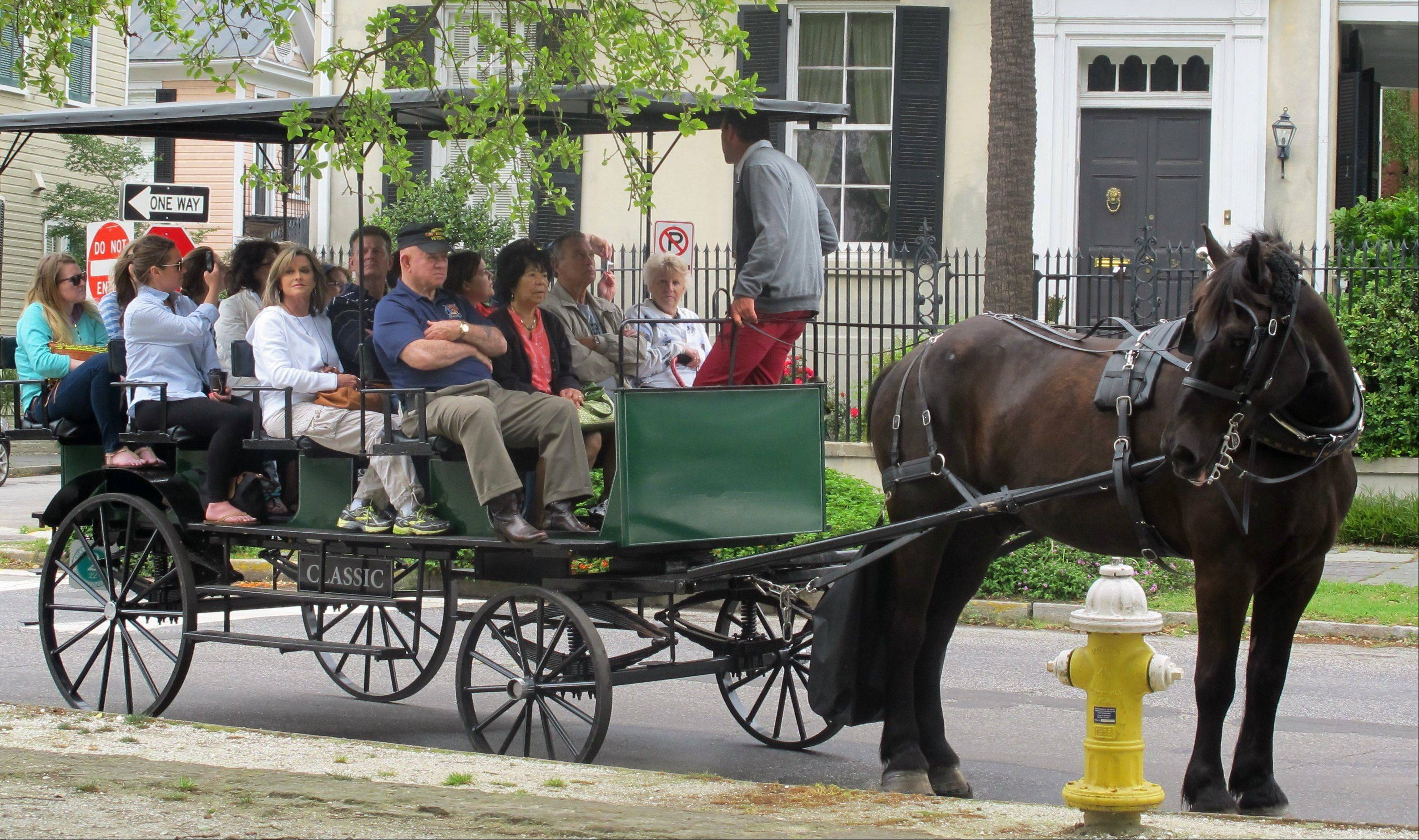 A carriage tour stops in front of a home in the historic Battery in Charleston, S.C. Charleston, the oldest city in South Carolina, was founded in 1670.