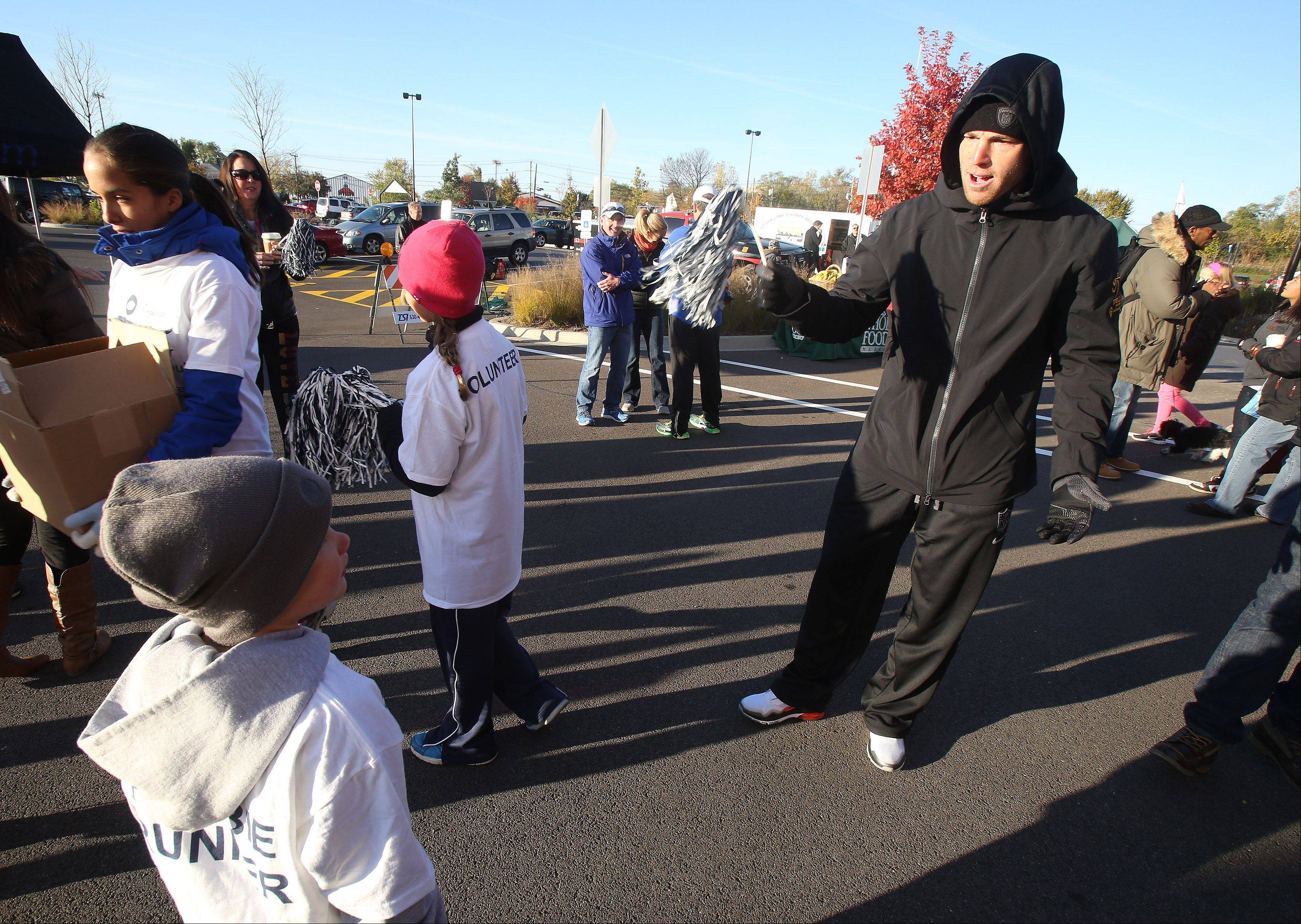 Chicago Bears kicker Robbie Gould cheers on a young fan Sunday during the Run for the Gould 5K and Kids Dash in Kildeer. Gould and TruCore Pilates sponsored the run to provide funds to the Goulden Touch charity which provides support to food banks, cancer research and other causes.