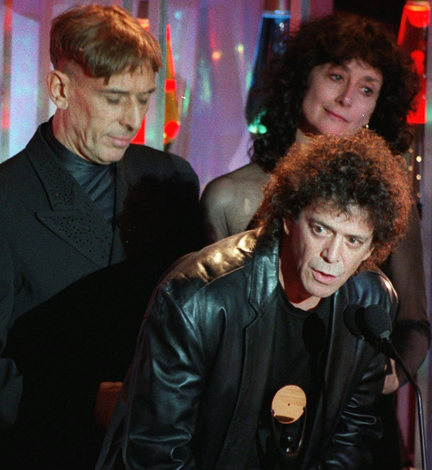 On Jan. 17, 1996, Lou Reed takes the podium as the Velvet Underground is inducted into the Rock and Roll Hall of Fame. Band mate John Cale is at left' at right is Martha Morrison, accepting for late band member Sterling Morrison.