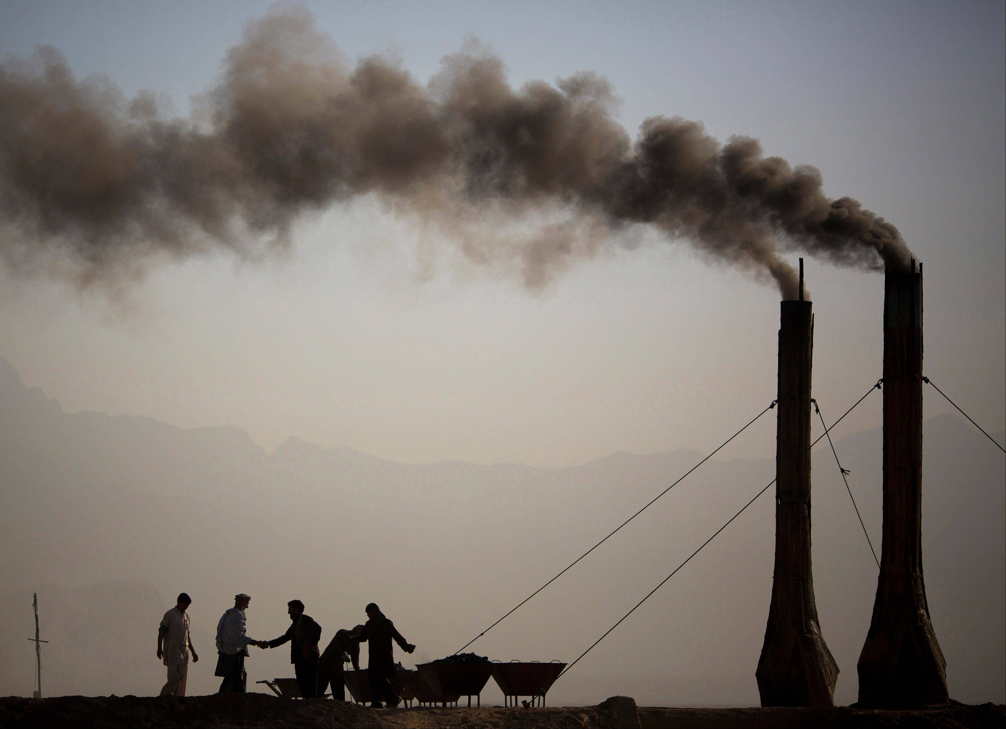 At a brick kiln, workers greet each other Saturday while preparing the kilns to fire bricks, early in the morning on the main highway leading to Bagram, on the outskirts of Kabul, Afghanistan. In the last two years, as U.S. and NATO troops prepare to leave Afghanistan, brick makers said business has drop
