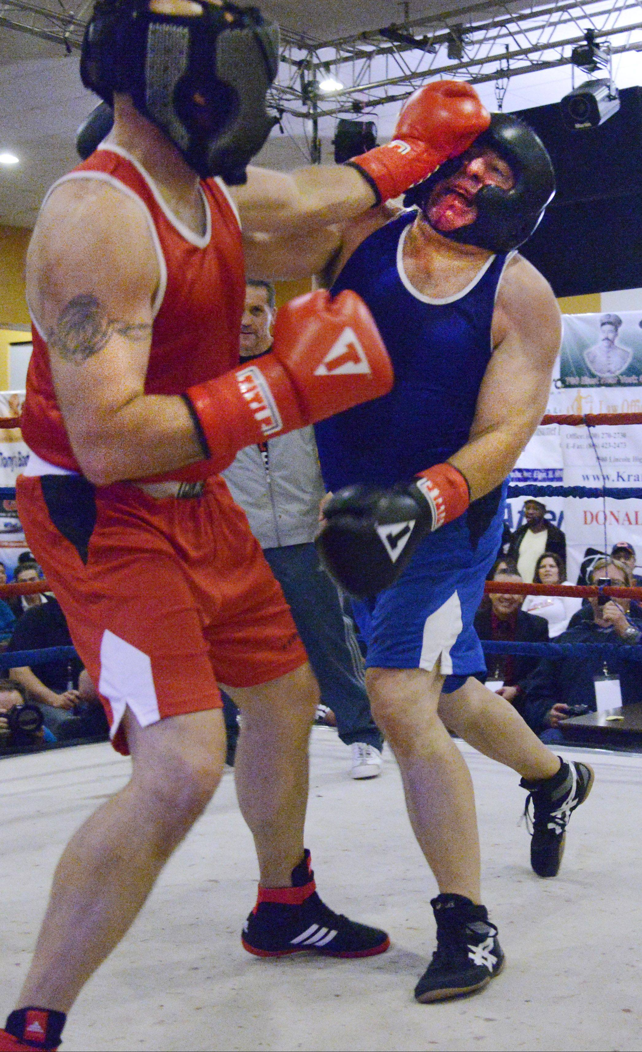 Oswego Police Chief Dwight Baird holds off Kane County Sheriff Pat Perez Sunday night at the 2nd Annual Tuition Knockout police boxing event in Aurora. Baird scored a technical knockout against Perez.