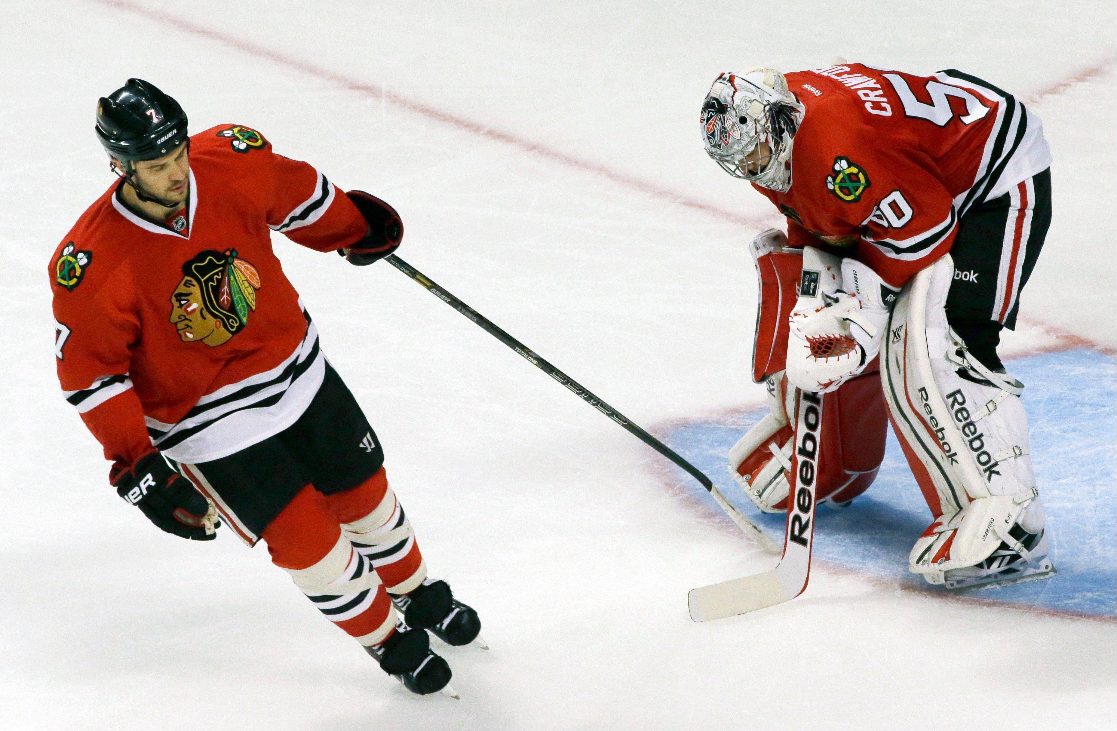 Brent Seabrook tries to cheer up to Blackhawks goalie Corey Crawford after Minnesota's Justin Fontaine scored during the third period of Saturday's 5-3 loss to the Wild at the United Center.