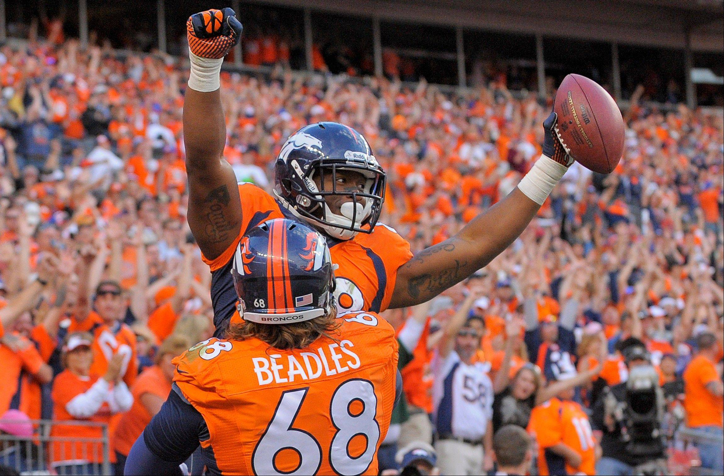 Denver Broncos wide receiver Demaryius Thomas (88) celebrates with guard Zane Beadles (68) after scoring a touchdown against Washington in the fourth quarter.