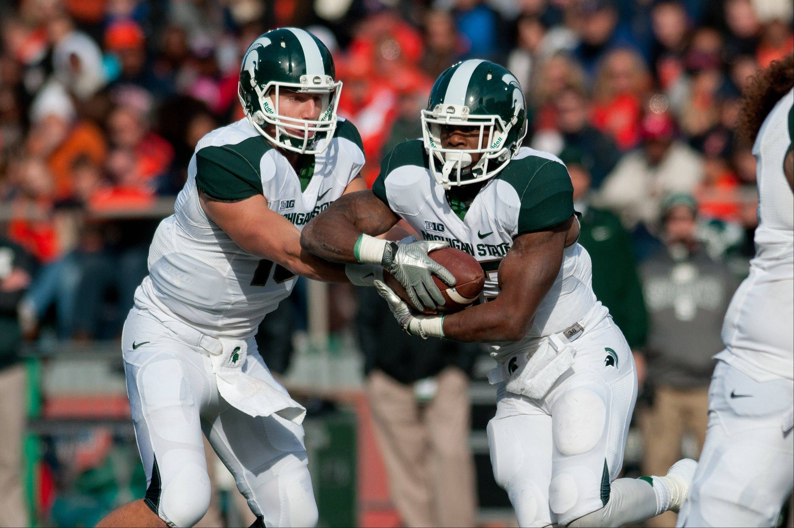 Michigan State quarterback Connor Cook (18) hands the ball off to running back Jeremy Langford (33) against Illinois during the first quarter of an NCAA college football game Saturday at Memorial Stadium in Champaign.