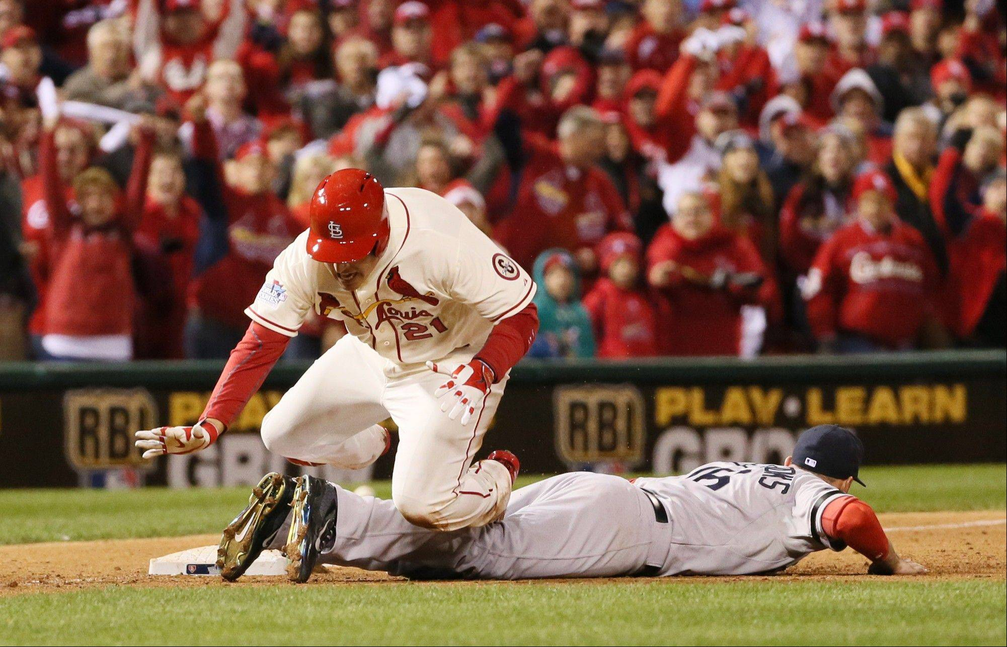 St. Louis Cardinals' Allen Craig trips over Boston Red Sox third baseman Will Middlebrooks as he tries to score from third in the ninth inning during Game 3 of the World Series. Craig was awarded home due to interference on the play.