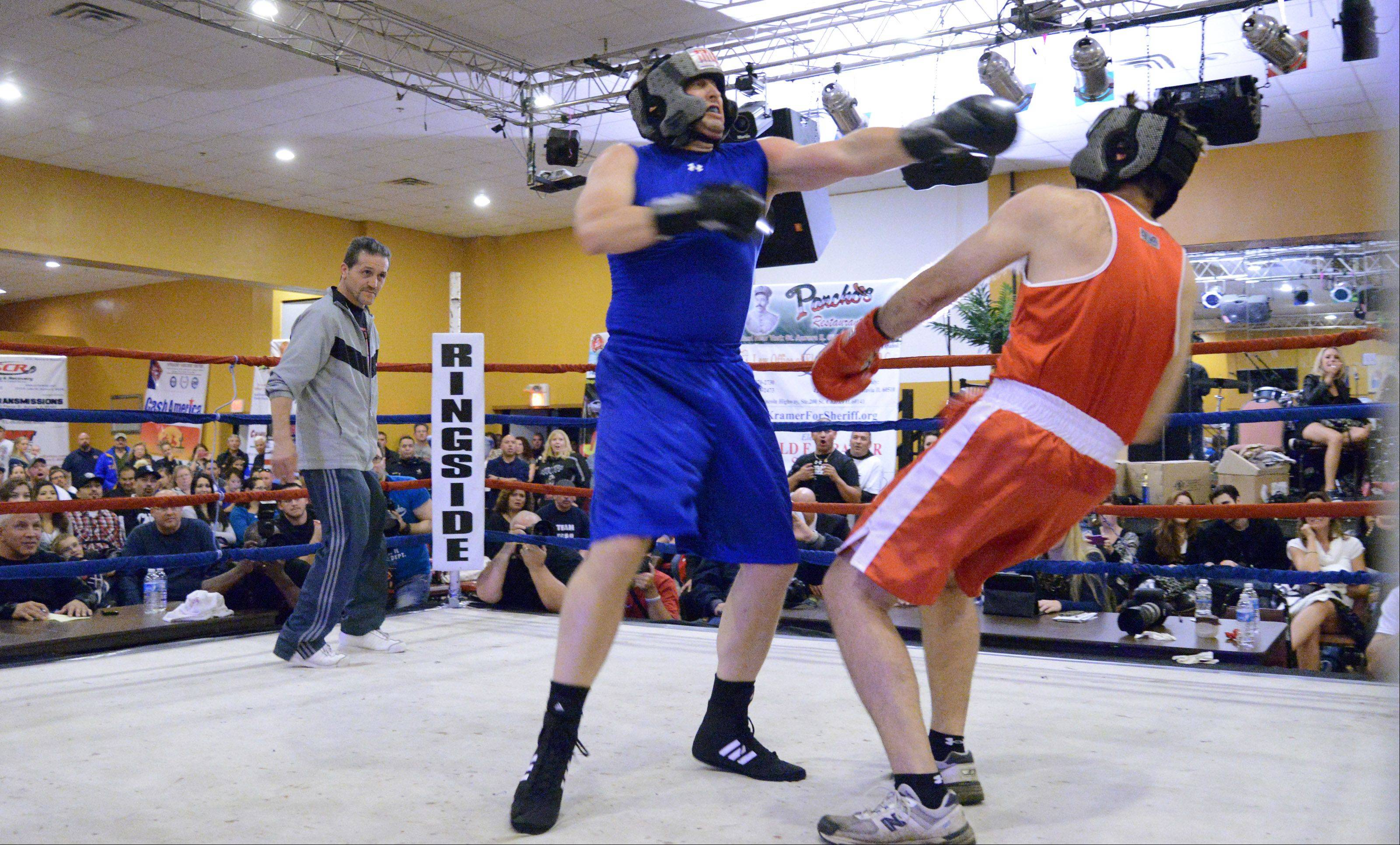 Elgin Police Chief Jeff Swoboda knocks down Aurora Police Chief Greg Thomas Sunday night at the 2nd Annual Tuition Knockout police boxing event in Aurora. The main event featured the two chiefs while earlier events featured other officers and investigators and officials.