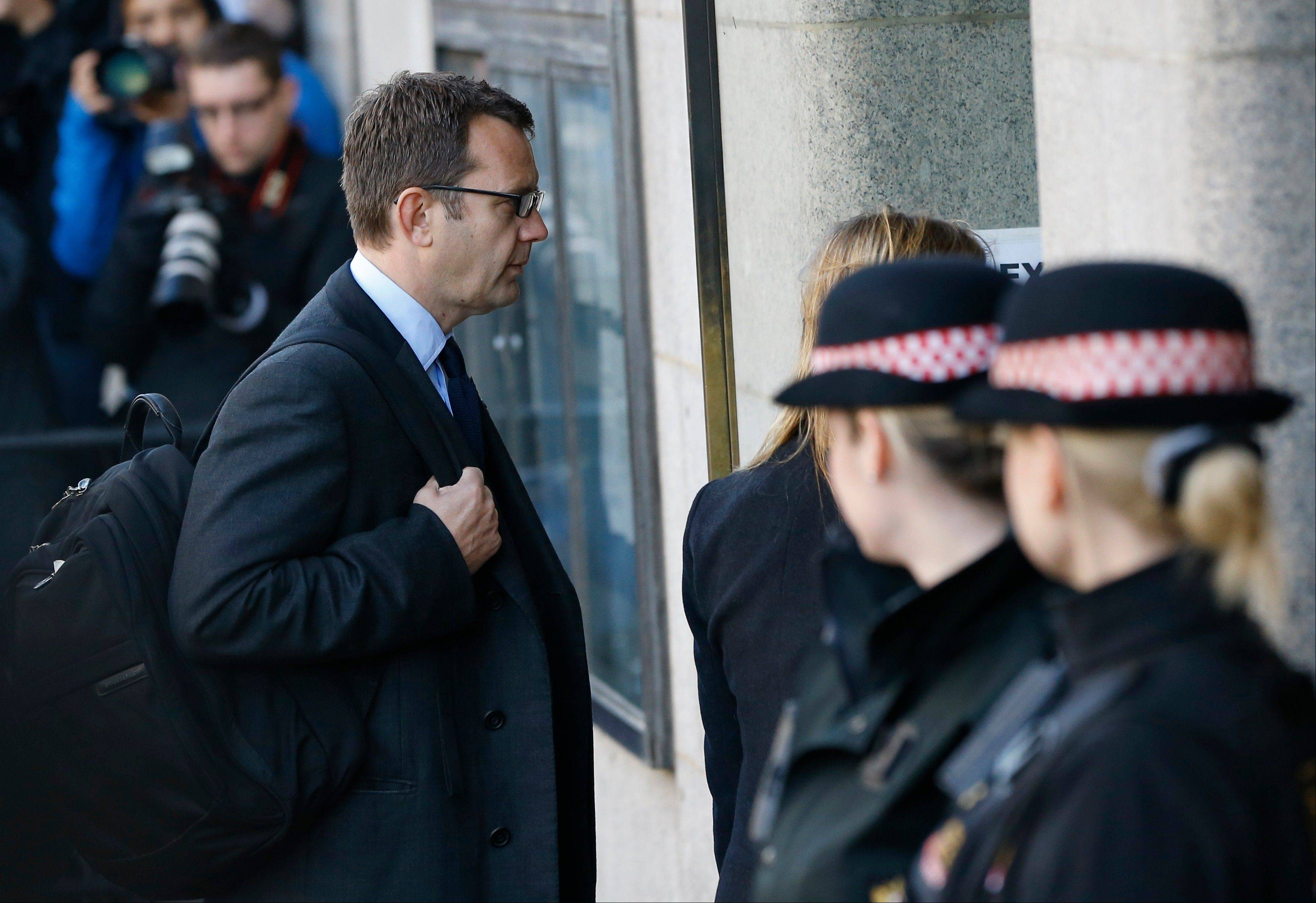 Andy Coulson is watched by police officers as he arrives at The Old Bailey law court in London, Monday. Former News of the World editors Rebekah Brooks and Coulson are due to go on trial Monday, along with several others, on charges of hacking phones and bribing officials while at the now-shuttered Murdoch tabloid.