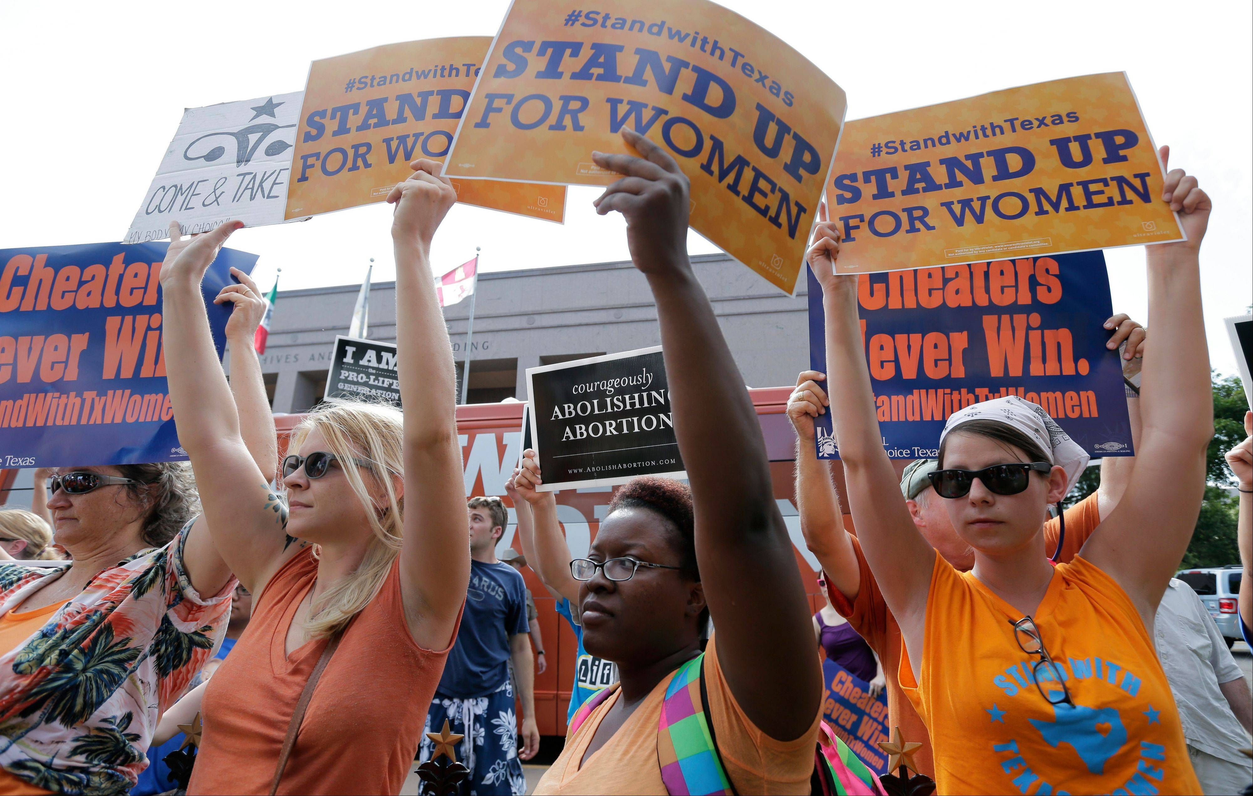 Opponents and supporters of an abortion bill demonstrate outside the Texas Capitol, in Austin, July 9. New abortion restrictions passed by the Texas Legislature are unconstitutional and will not take effect as scheduled Tuesday, a federal judge has ruled.