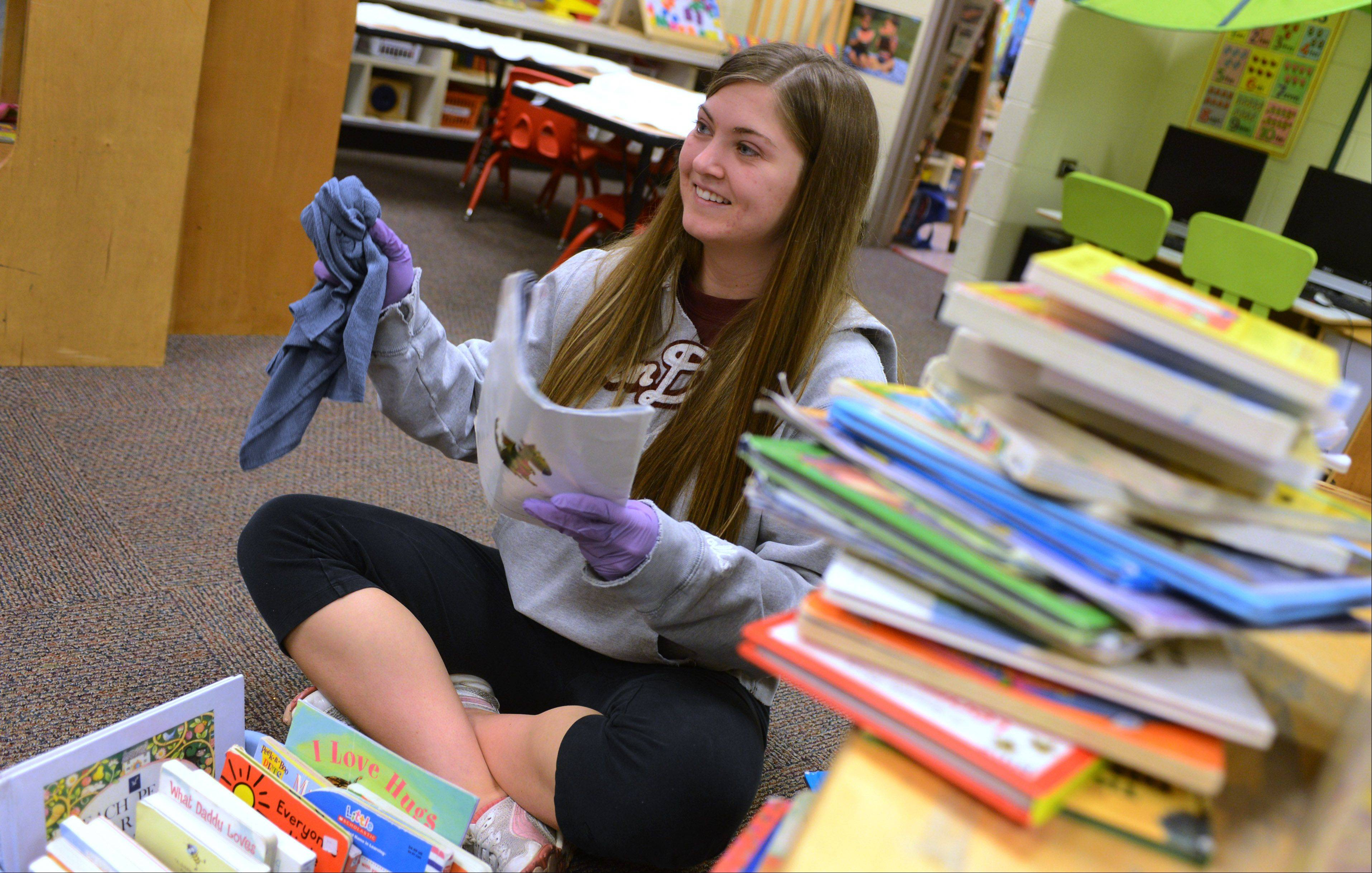 Antioch resident Katie Graziano wipes down books in the College of Lake County Children's Learning Center Saturday during the Make a Difference Day in Grayslake. Graziano is also a student at the college.