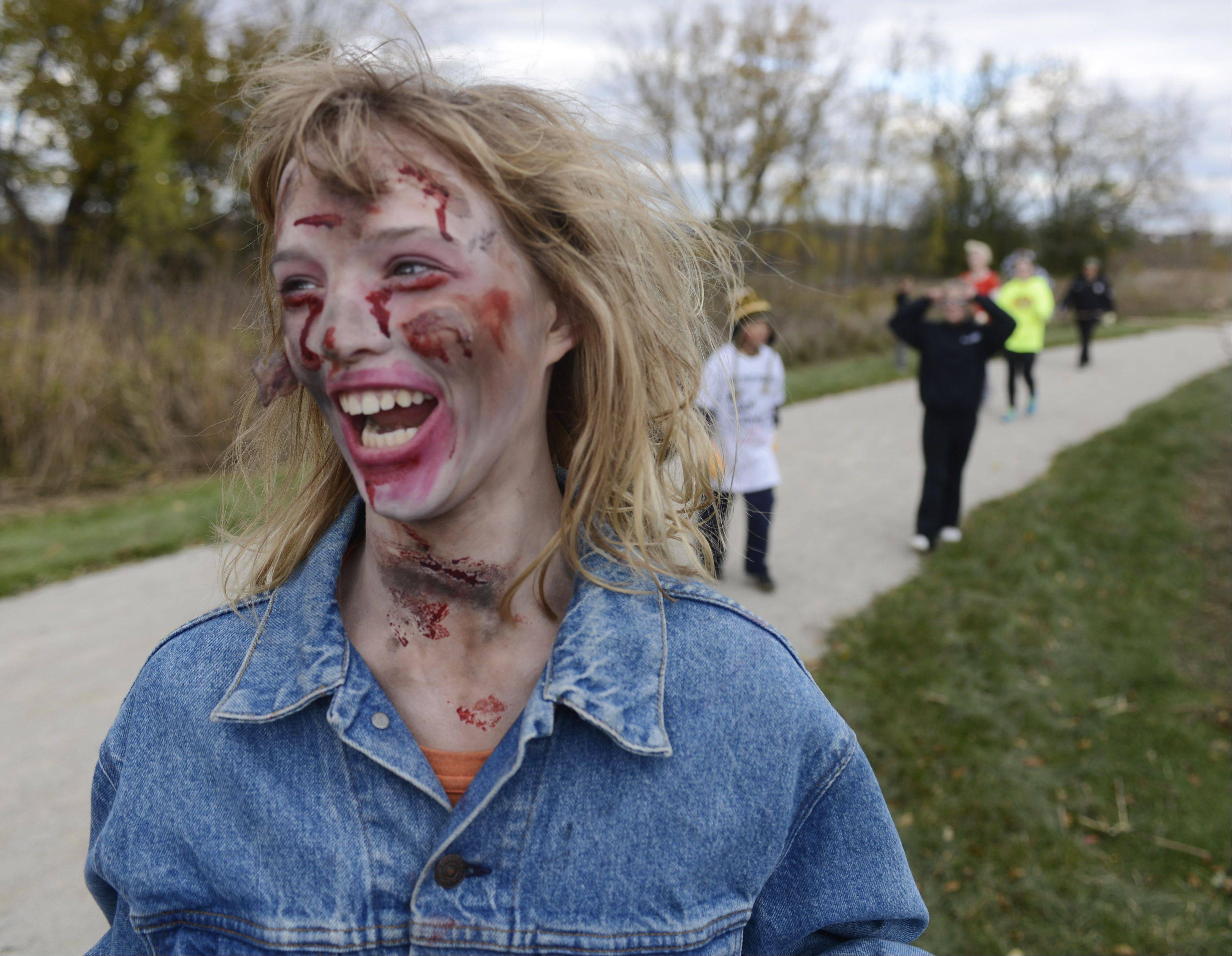 "Zombie Emily Finger of Naperville searches for victims during the Zombie Outbreak Dash, held at Bartlett Nature Center, James ""Pate"" Phillip State Park in Bartlett Saturday."