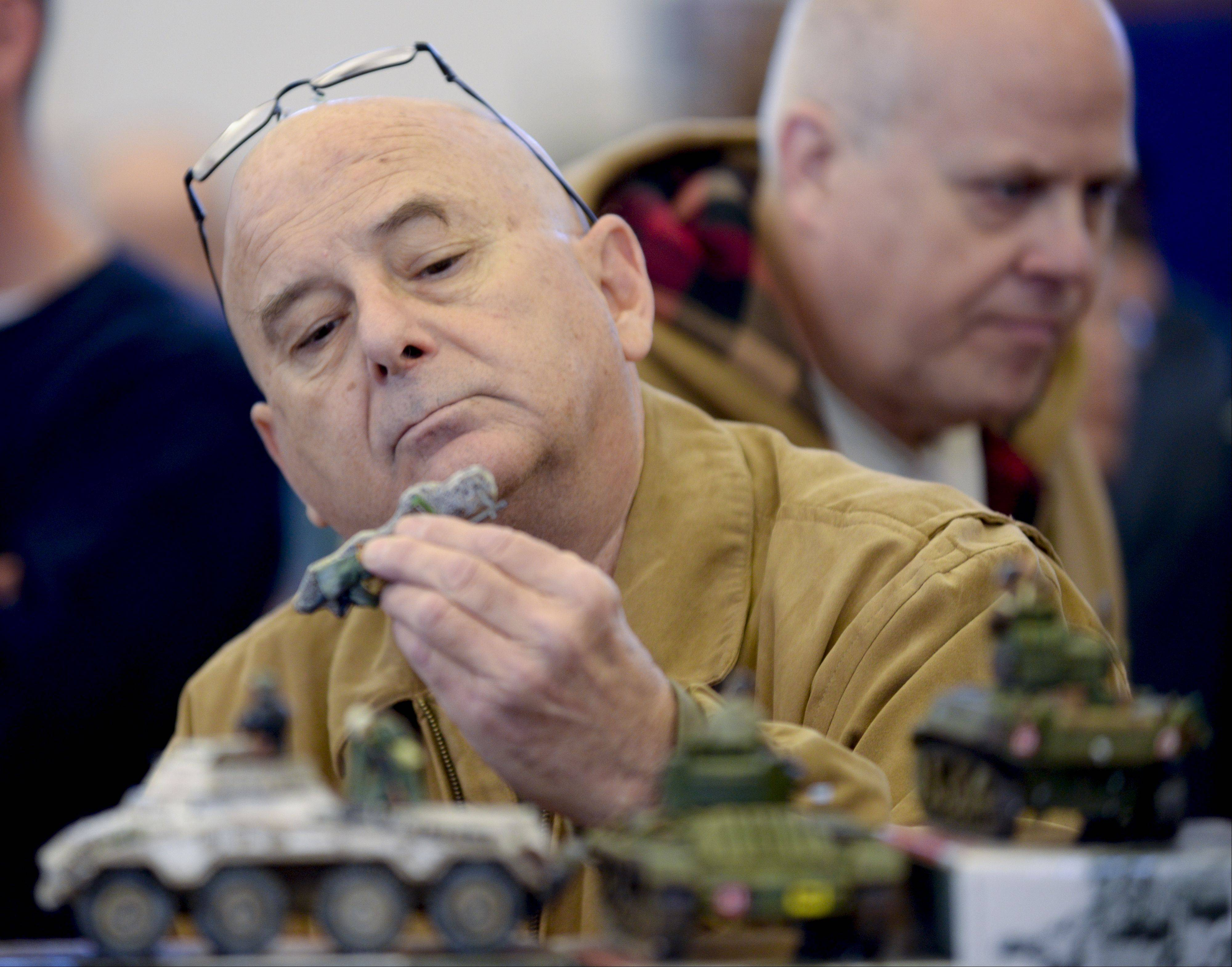 Tom Zinschlag of Bartlett buys some military figures at the 40th annual Antiques and Collectibles Toy and Doll Show at the Kane County Fairgrounds Sunday.