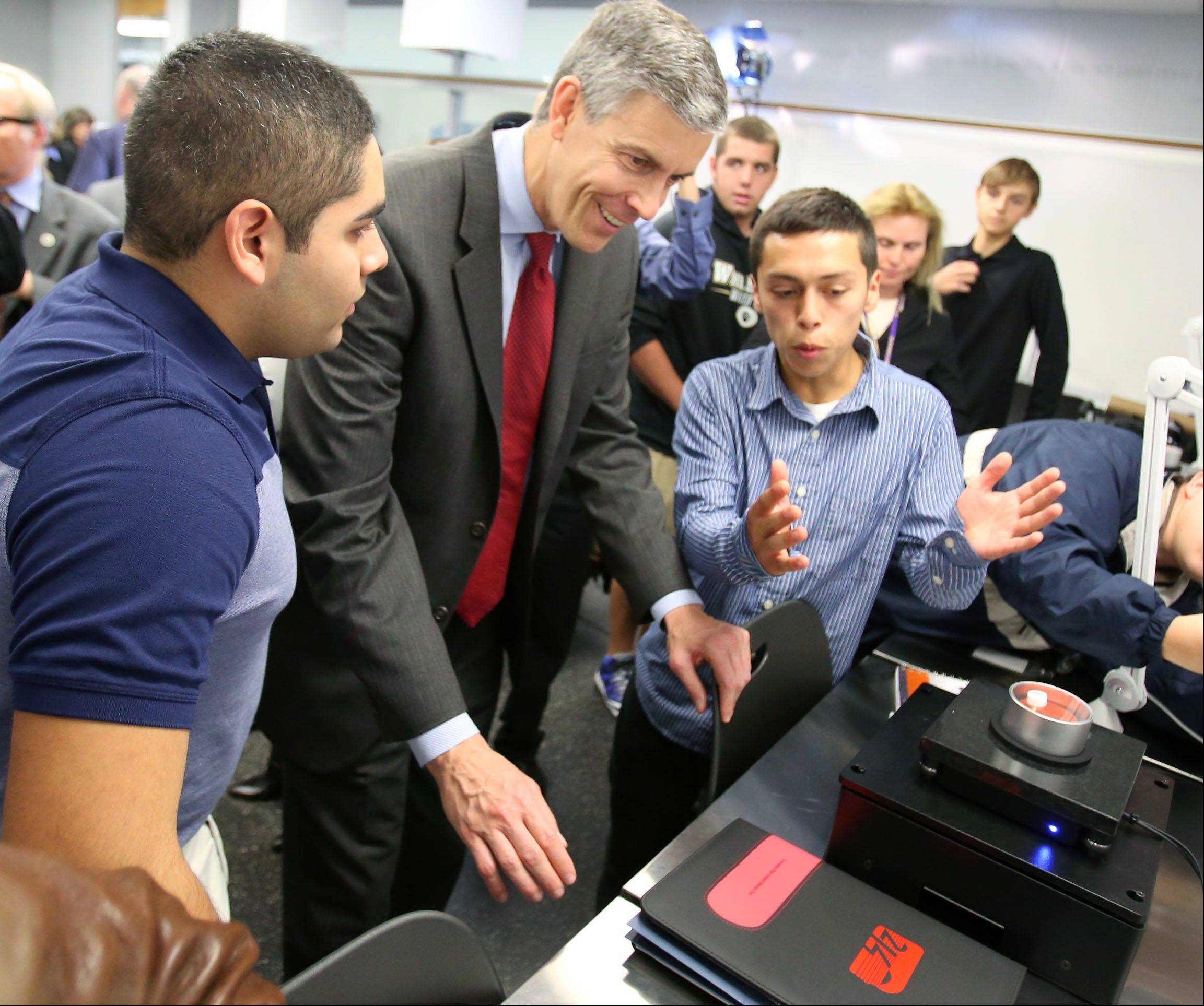 Wheeling High School seniors Alex Lopez, left, and Alfredo Rocha explains nano technology equipment to Secretary of Education Arne Duncan while touring of the school's new nano technology lab in Wheeling on Thursday.