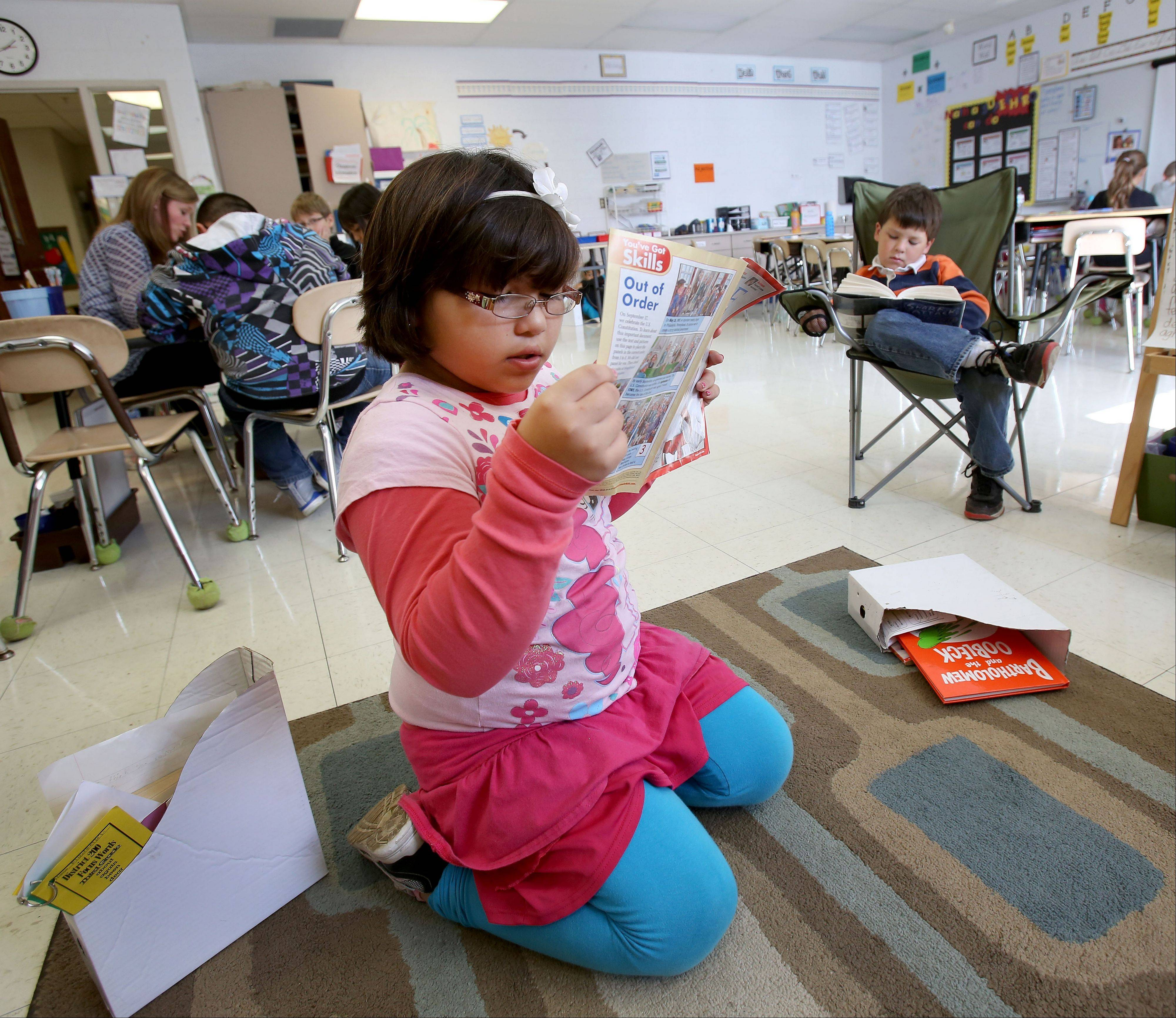 Elizabeth Torres, left, and Teddy Ritchie, right, find good reading spots in their third-grade classroom at Longfellow Elementary in Wheaton. It is one of the schools that saw the smallest point decrease in the percent of students who meet or exceed state standards in the first year the cutoff score to qualify as meeting standards was raised.